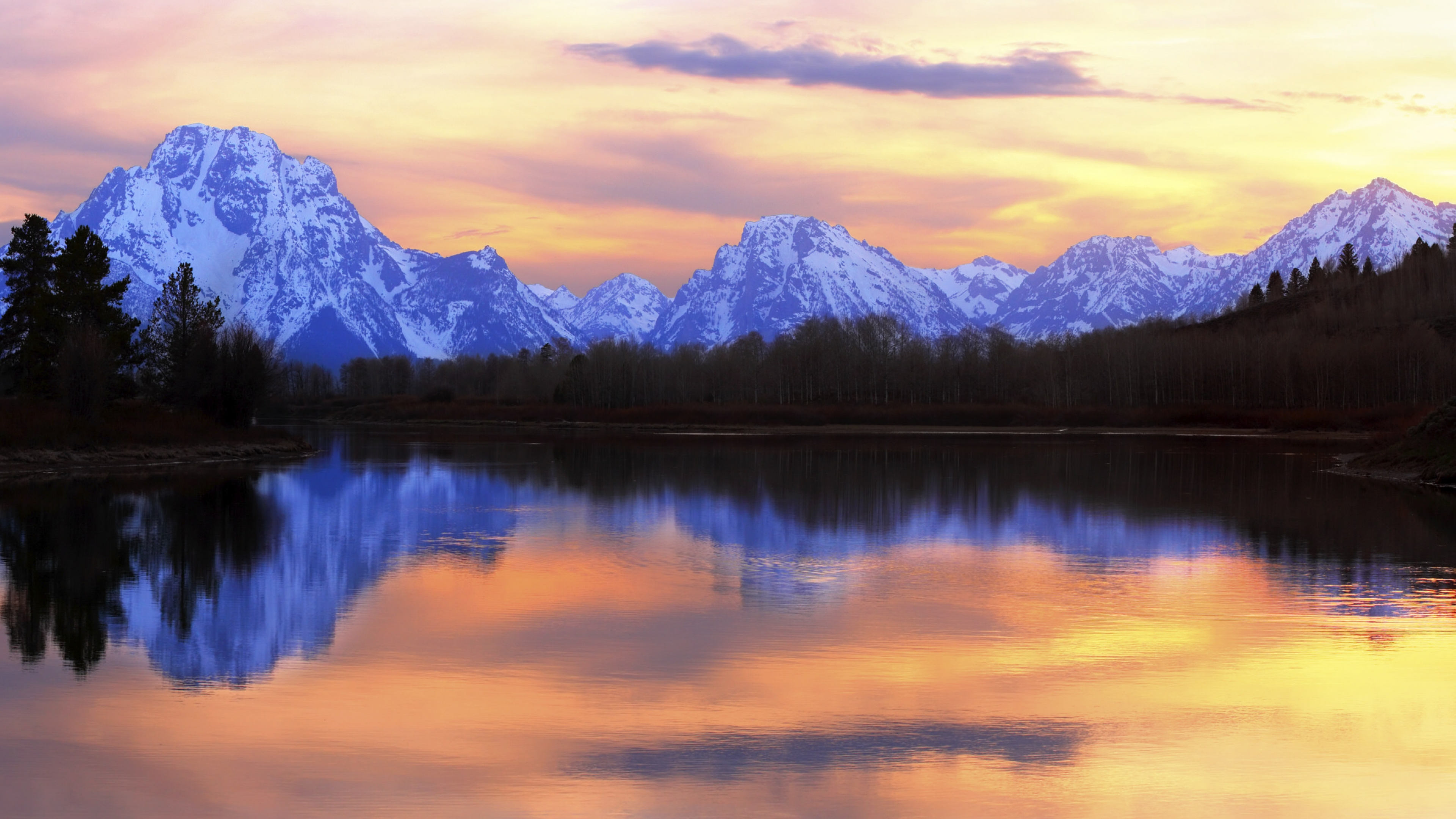 An orange, yellow, and purple sky reflected in a still lake with the snow-covered Grand Teton mountains in the background