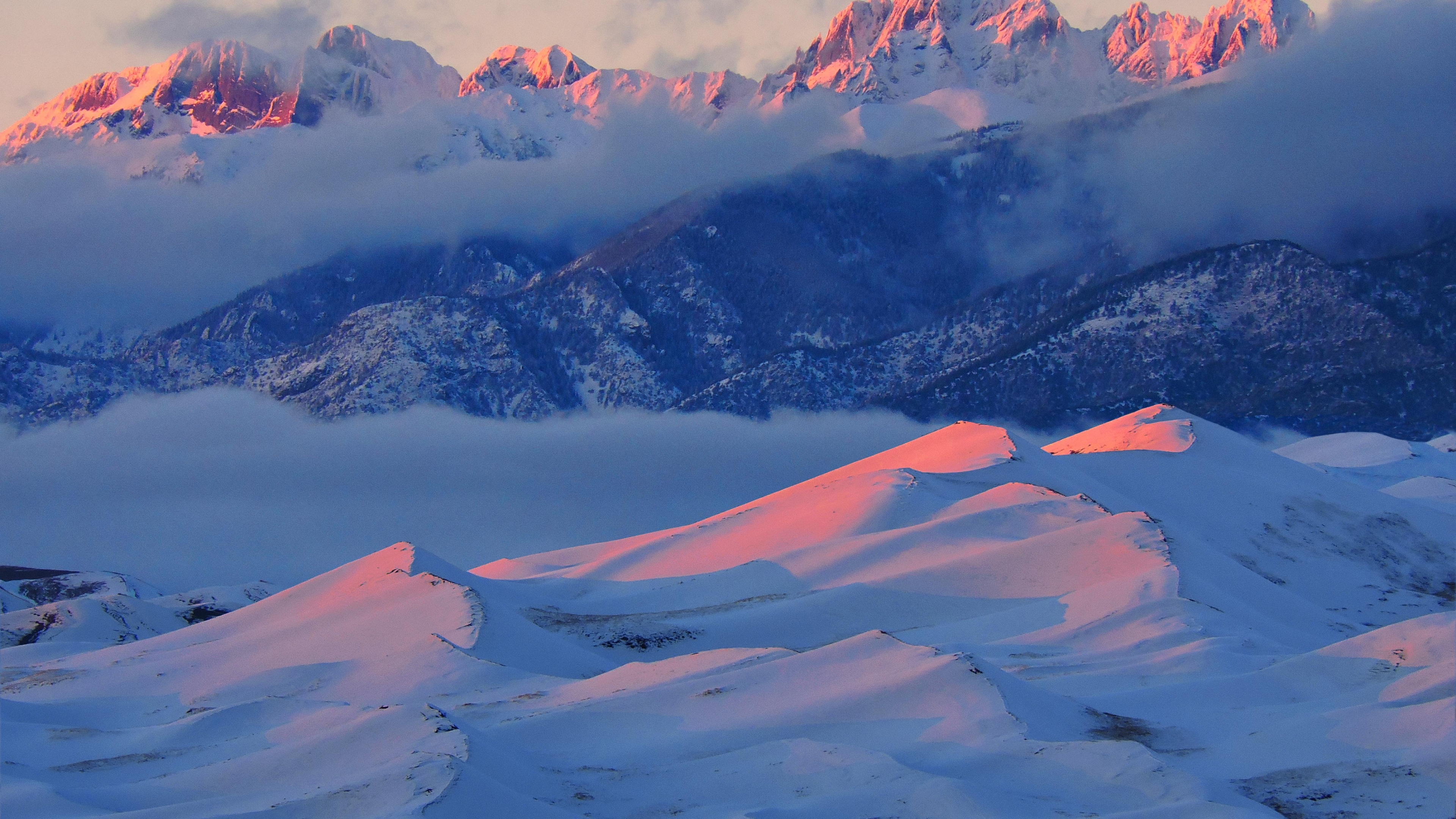 Redish-orange alpenglow lighting up the snow-covered mountains and snow-covered sand dunes at Great Sand Dunes National Park and Preserve