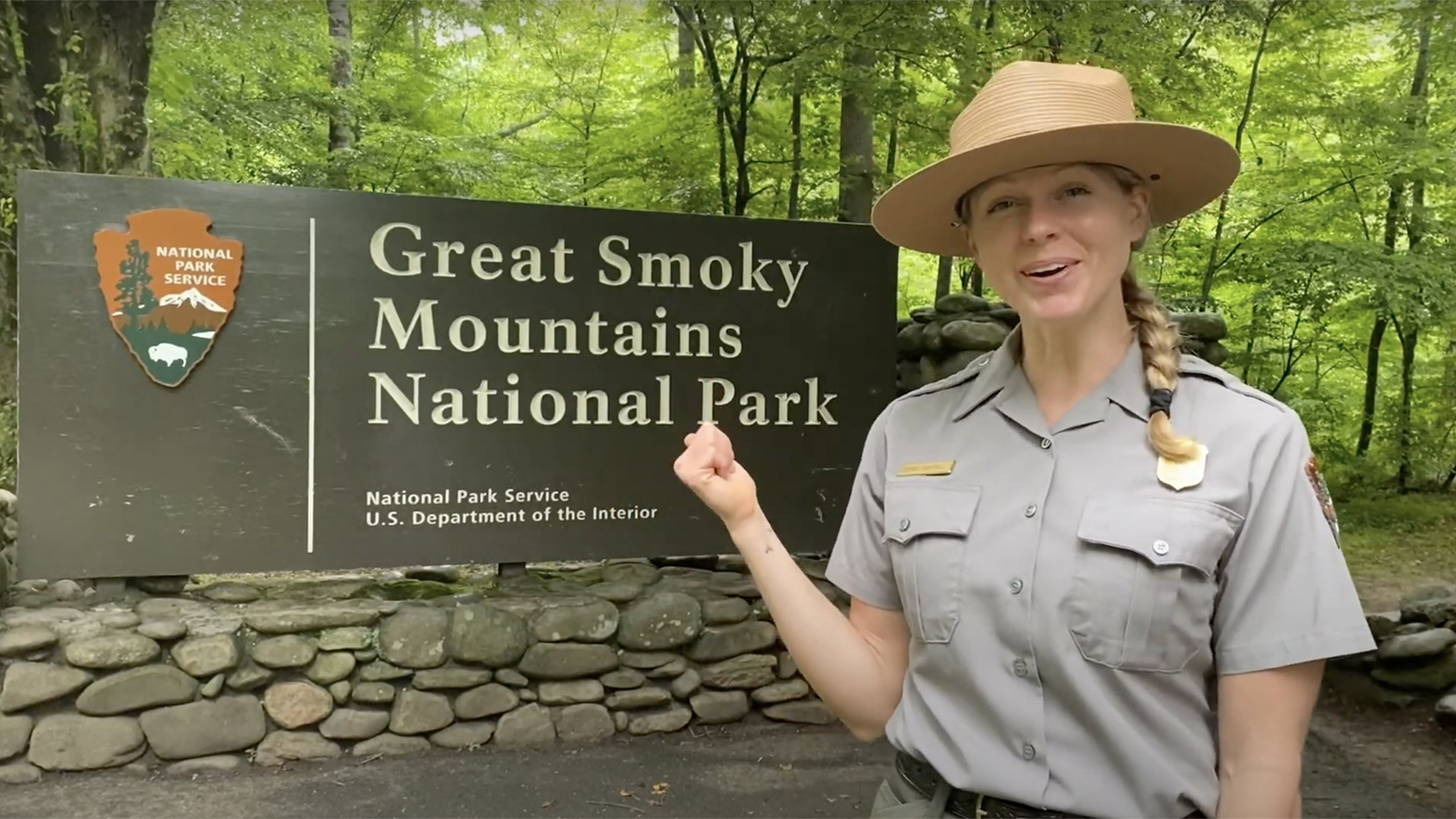A ranger stands in front of the entrance sign to Great Smoky Mountains National Park
