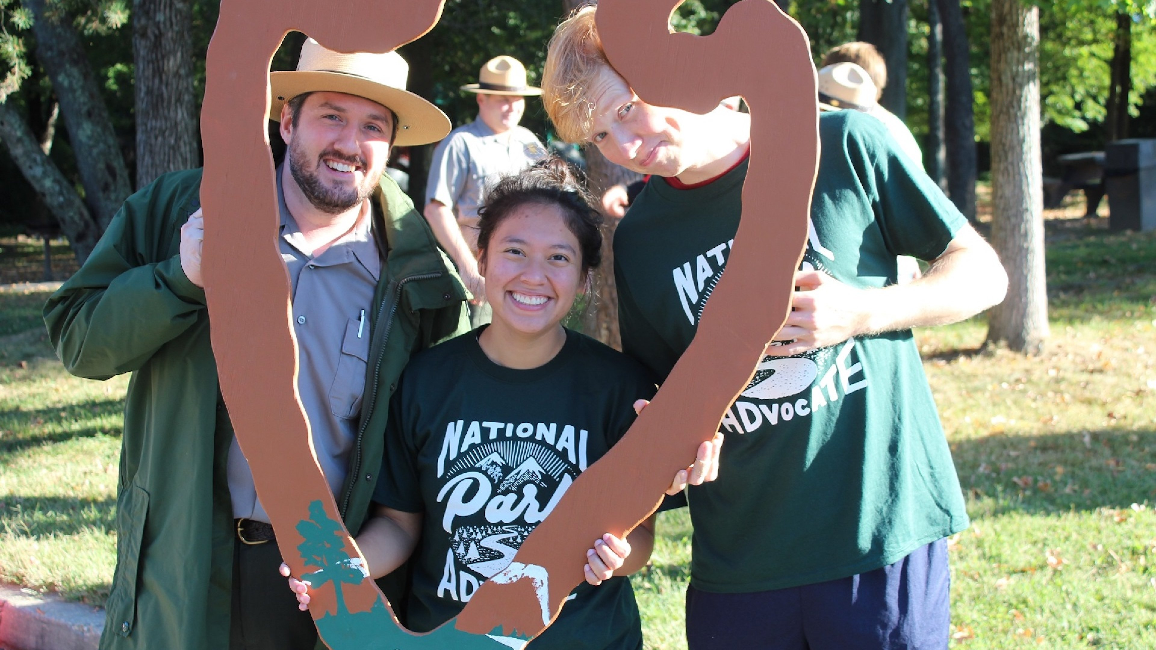 Volunteers for National Public Lands Day at Greenbelt Park posing inside a National Park Service Arrowhead