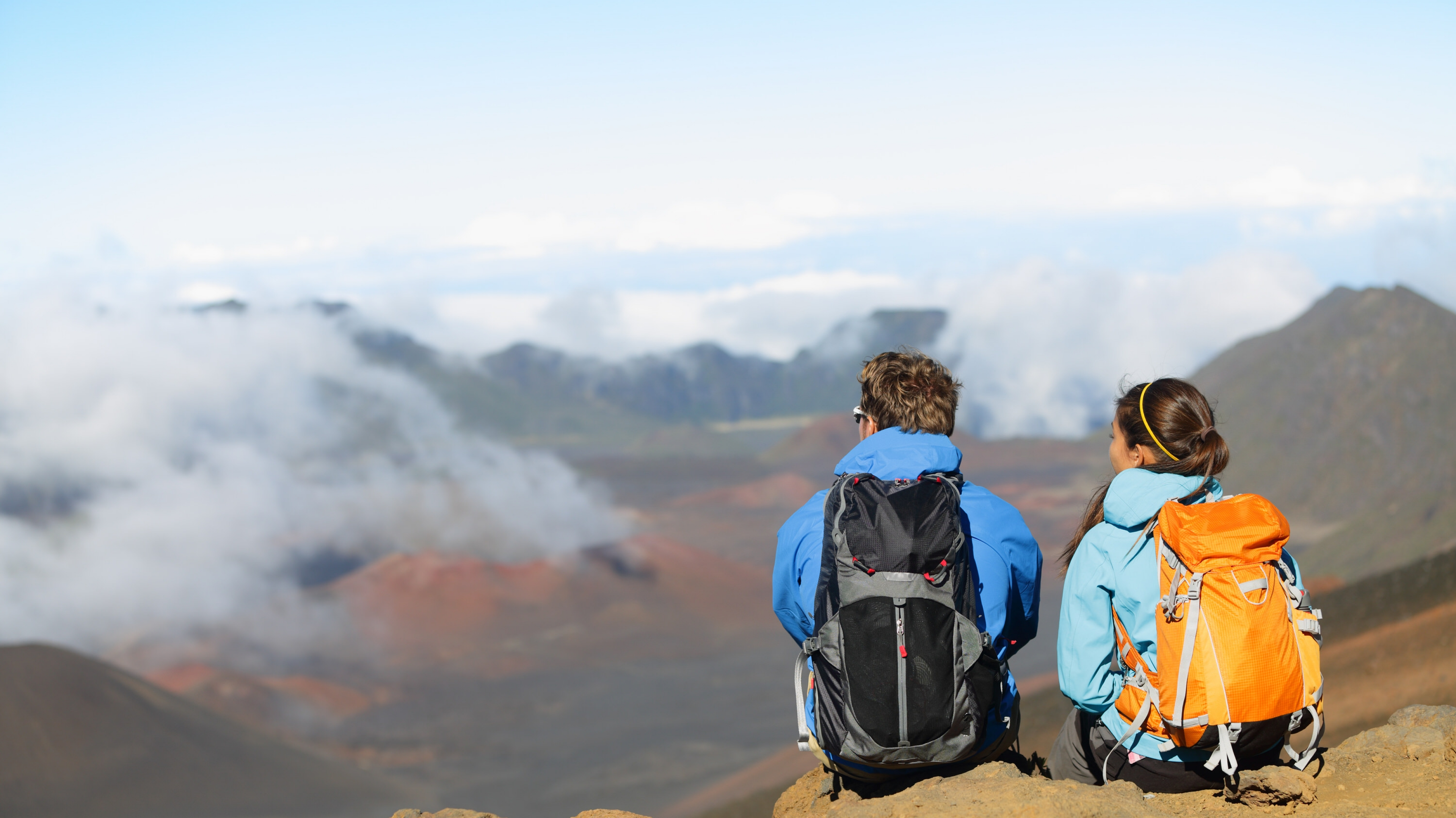 A couple sitting on top of a mountain looking down at a valley at Haleakala National Park