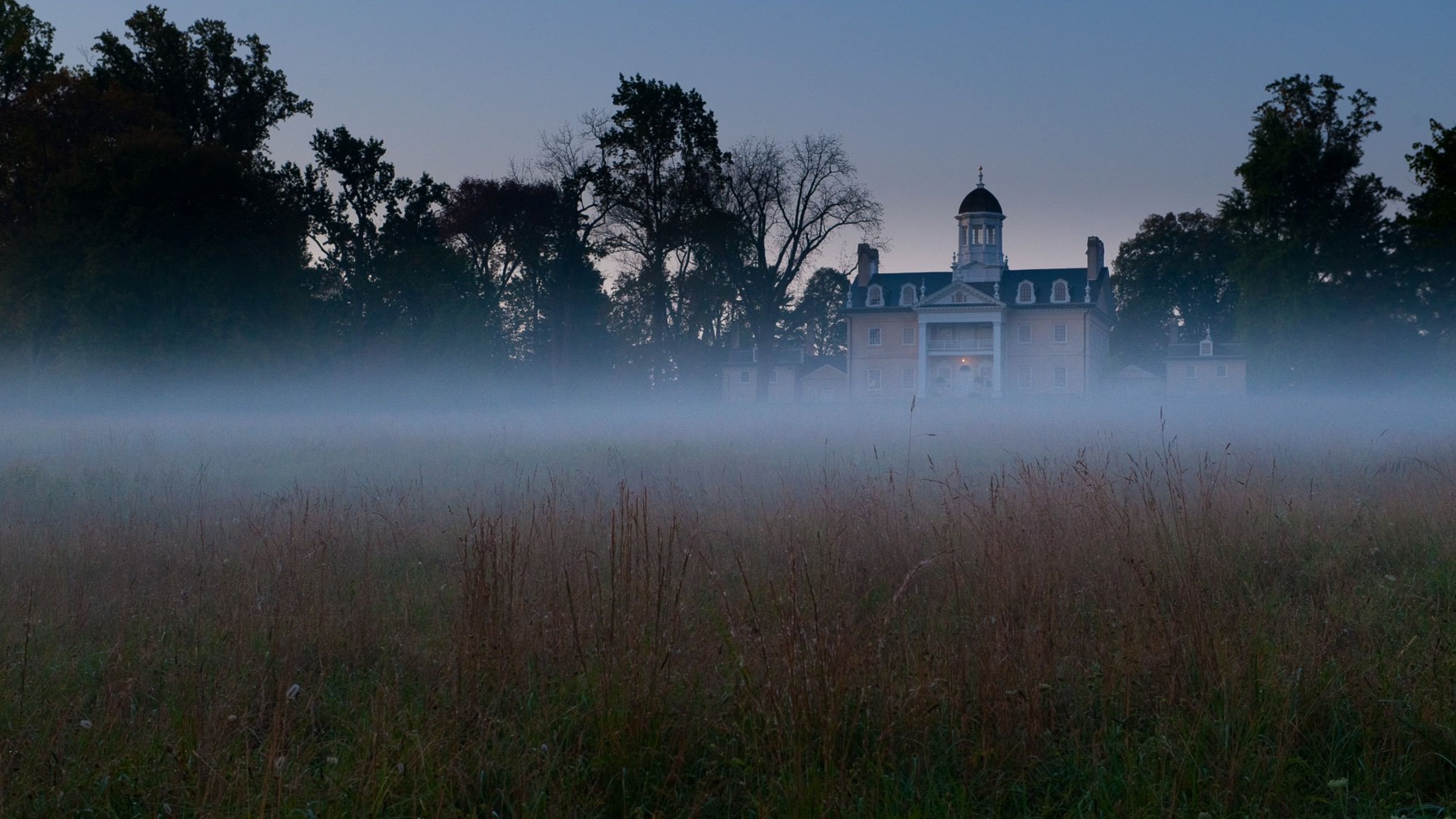 An eerie photo of the Hampton National Historic Site in the distance behind a foggy field at dusk