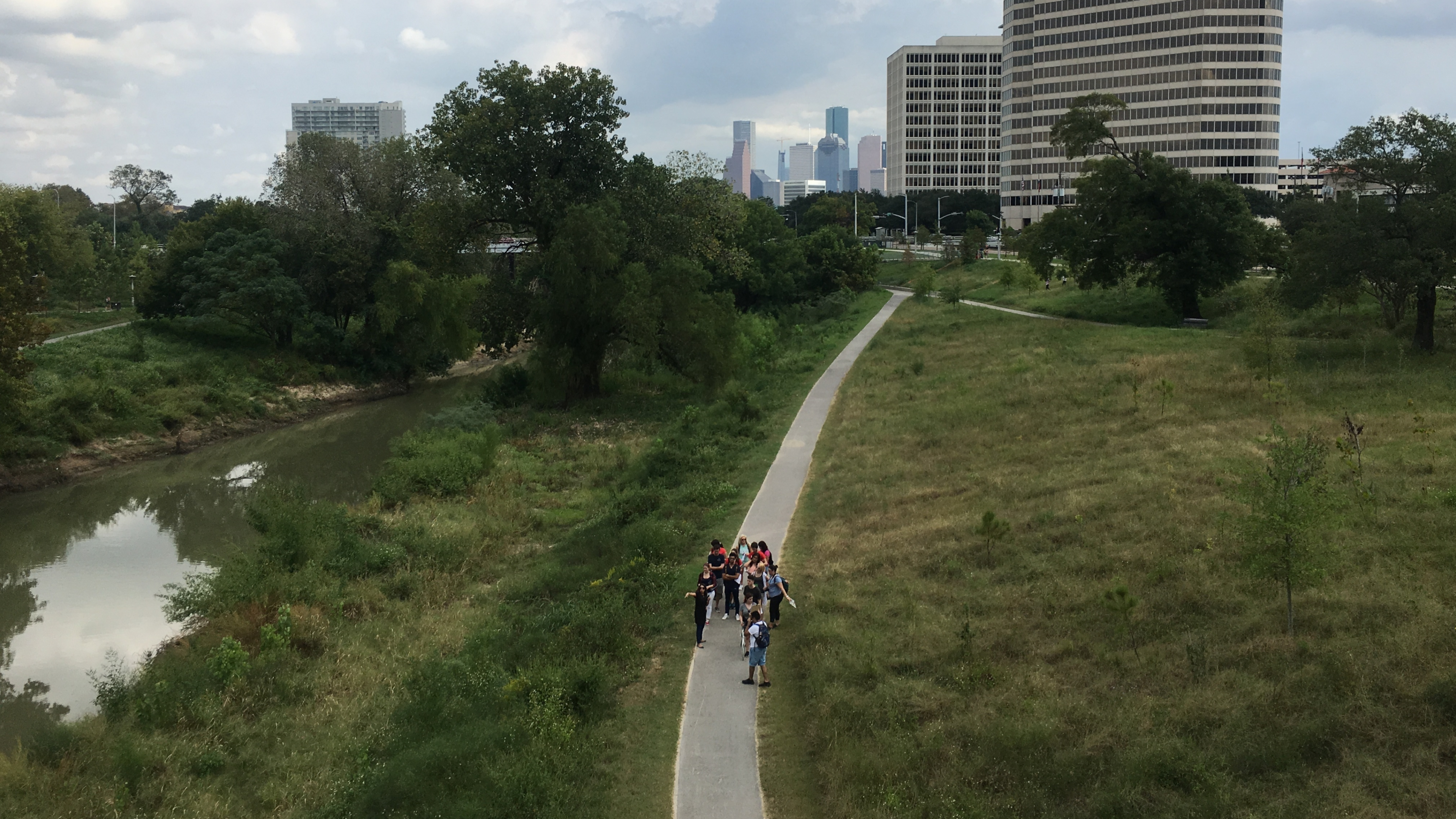 Looking down on children walking on a boardwalk down a grassy field with the high-rises of Houston on the background