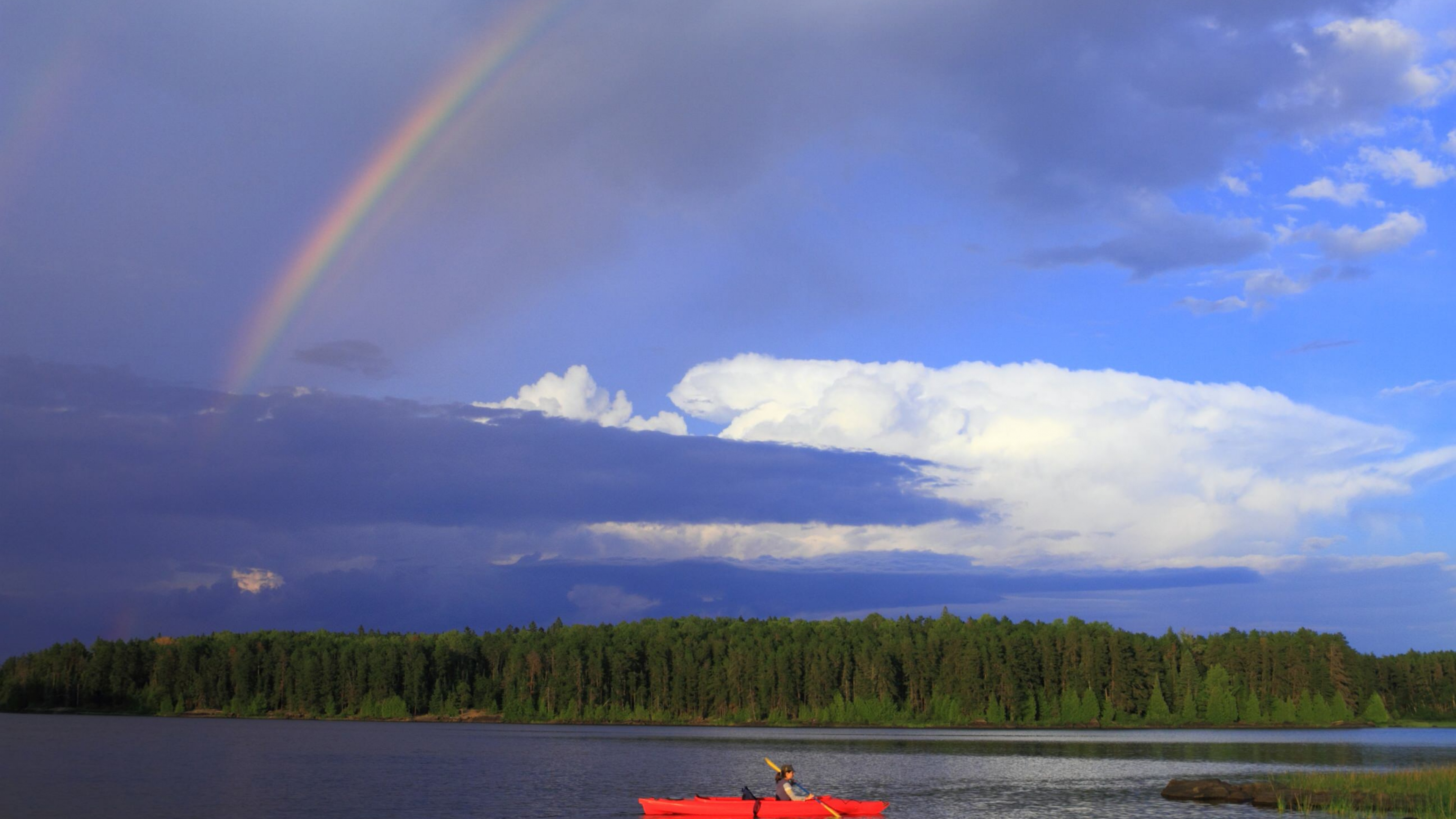 Canoeing on the lake at Voyageurs National Park, Minnesota, with a rainbow