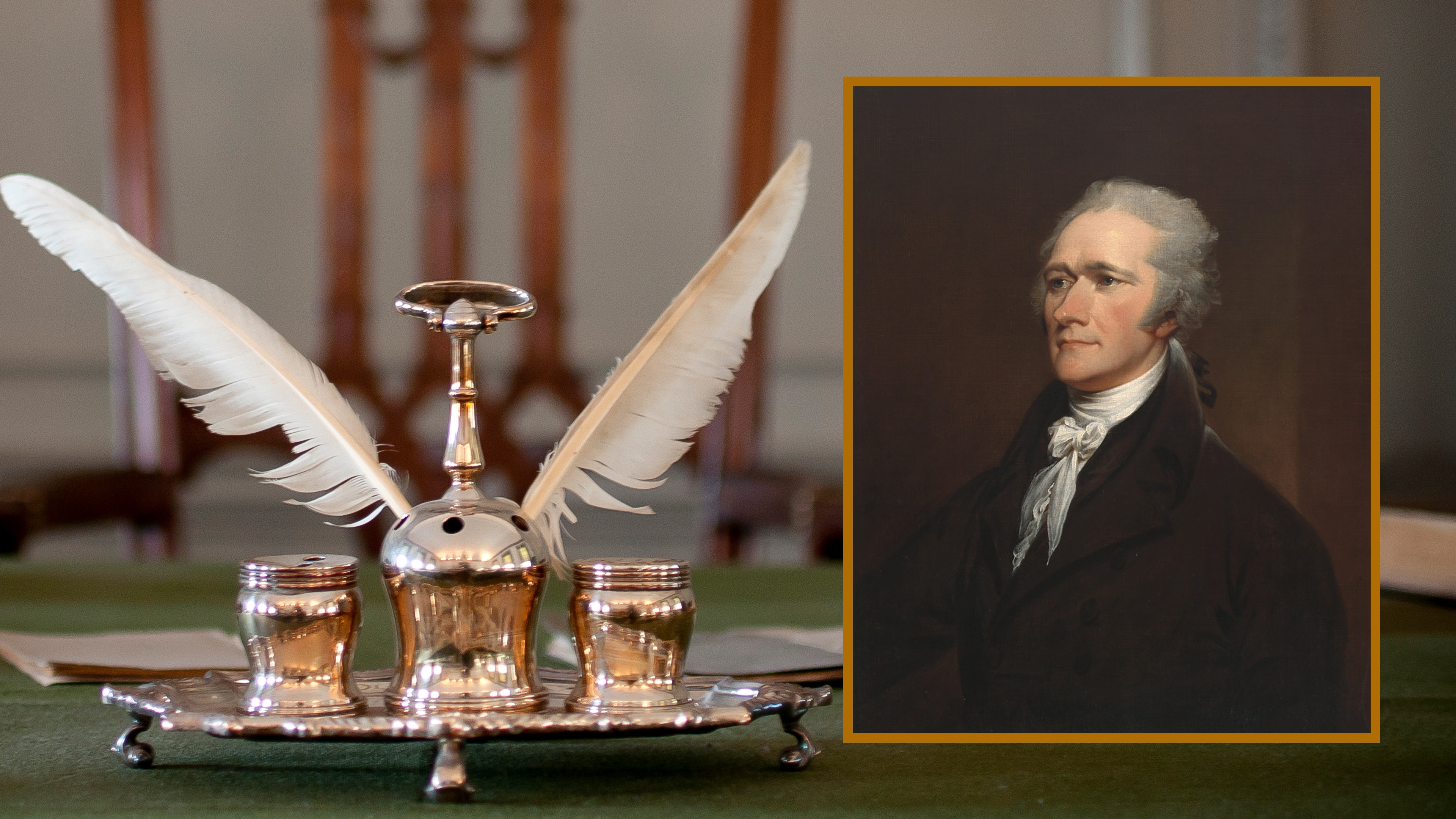 Syng Inkstand, with feather quills poised in a polished silver inkstand on a green velvet desktop, with a wooden chair in the background. Superimposed: Alexander Hamilton's portrait is framed on the right side.