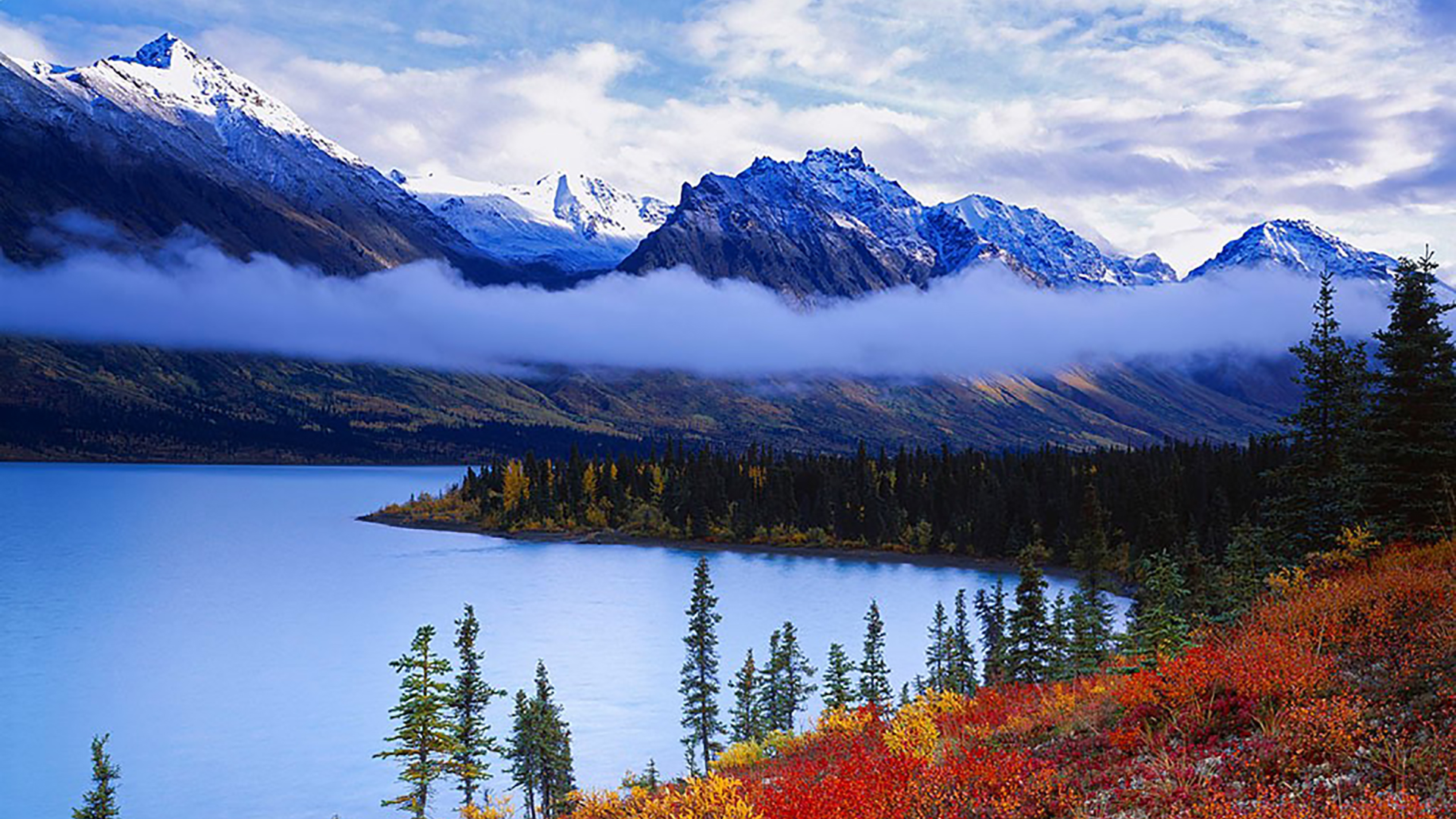 Low clouds hang over a crystal blue, still lake. In the foreground, autumnal colored leaves cover rolling hills