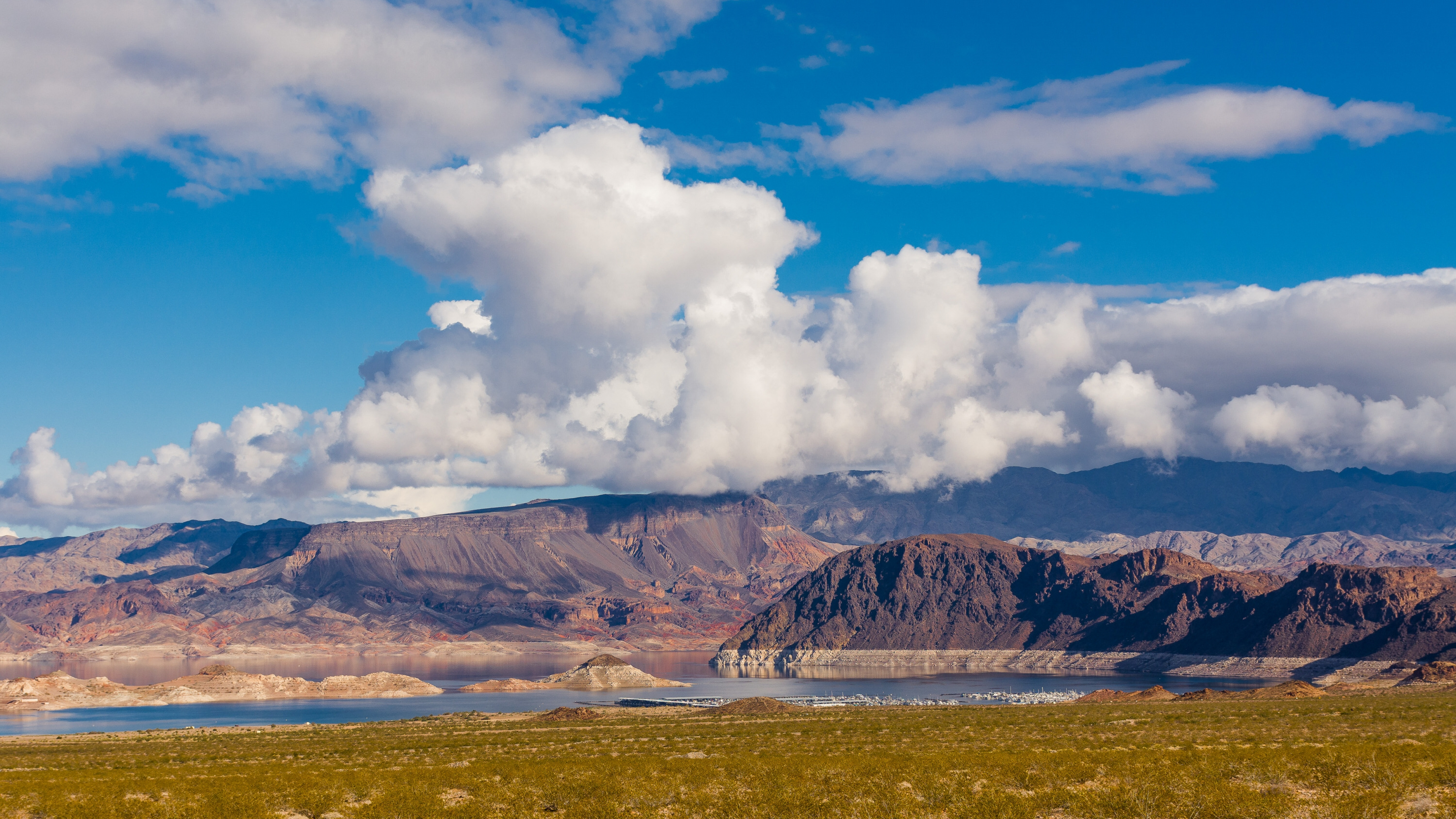 White clouds in blue sky over the red rock mountains of the Boulder Basin at Lake Mead National Recreation Area