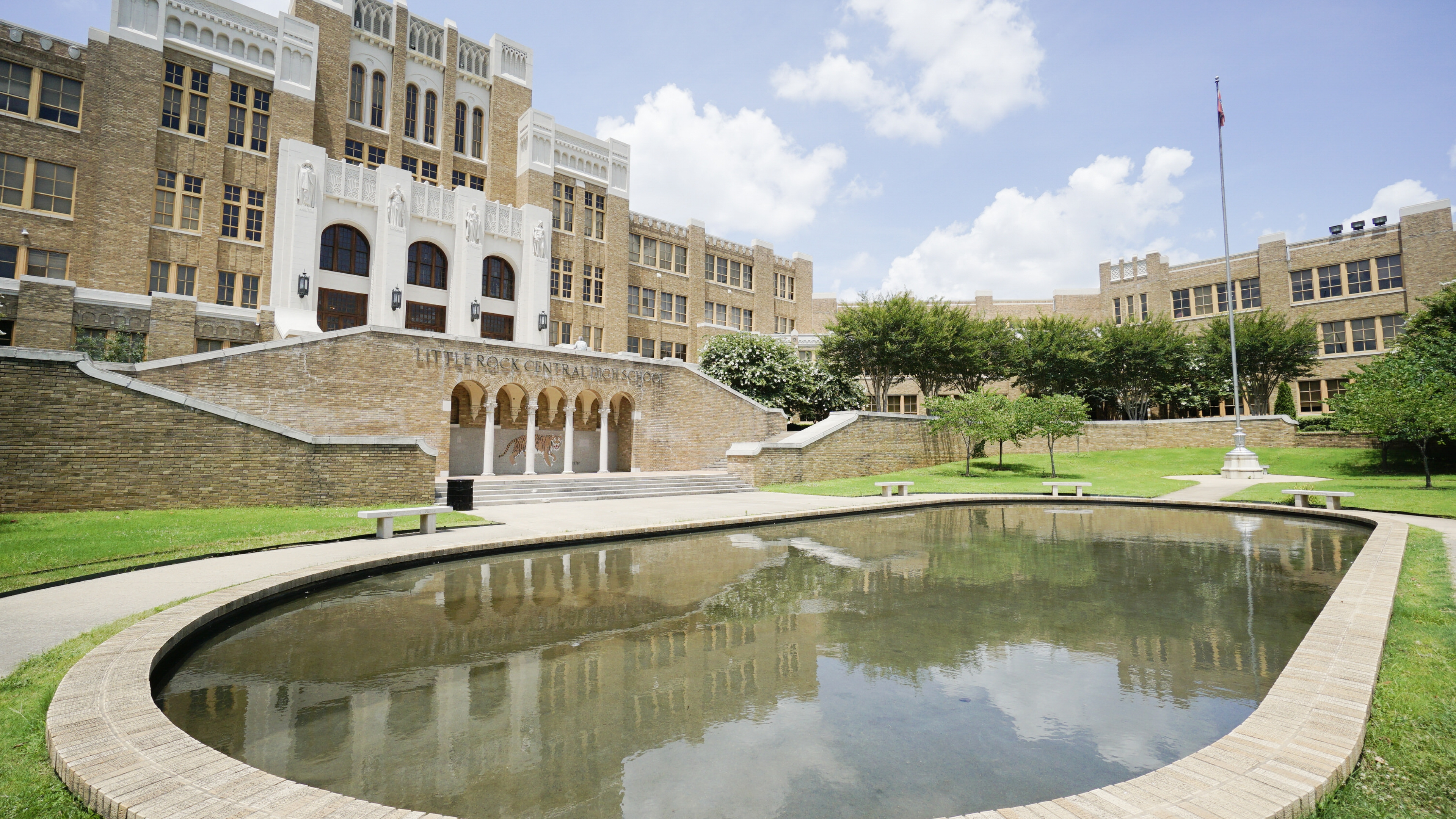 The brick and concrete buildings of Little Rock Central High School National Historic Site behind a big pool reflecting pool