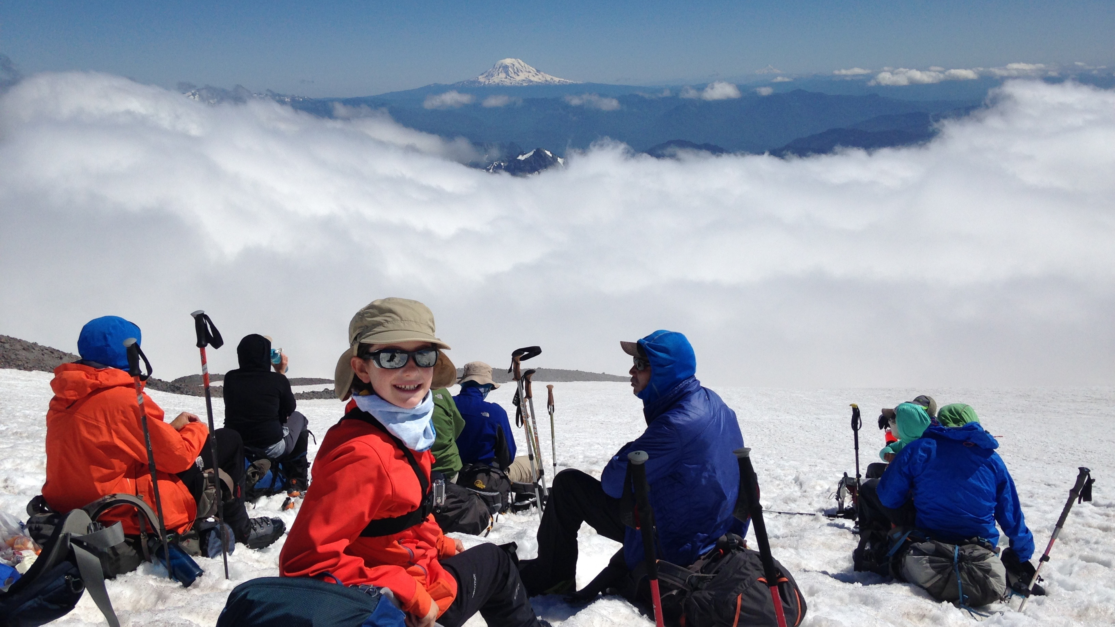 Lucy sitting on her backpack on the mountain, looks back at camera and smiles, wearing winter gear