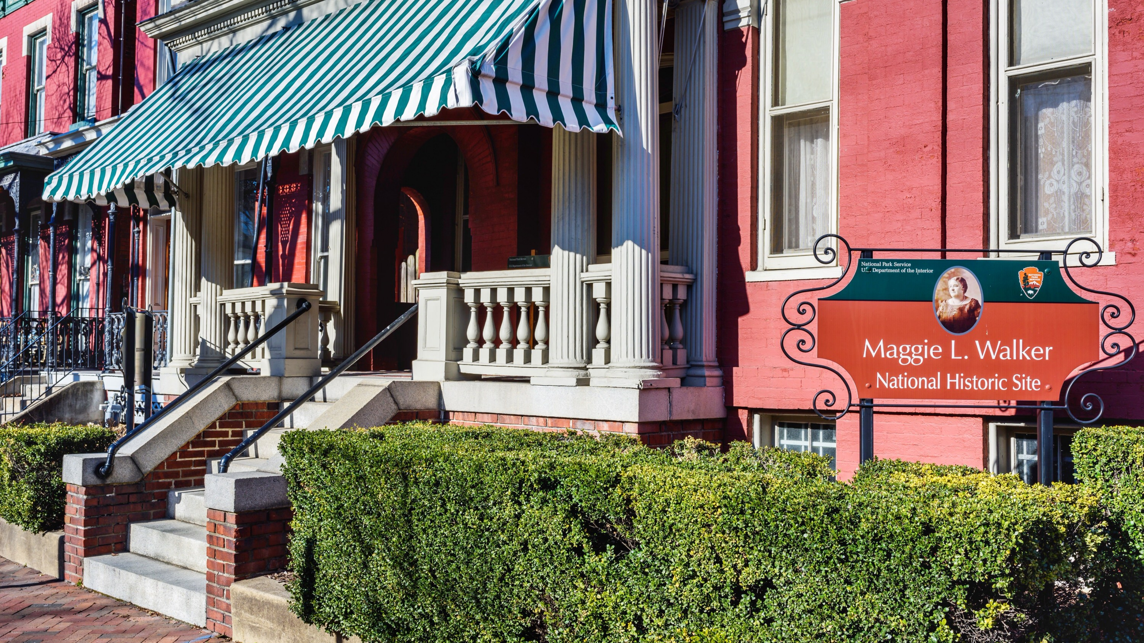 A view, from the sidewalk, of the striped awning hanging over the entrance to Maggie L. Walker National Historic Site