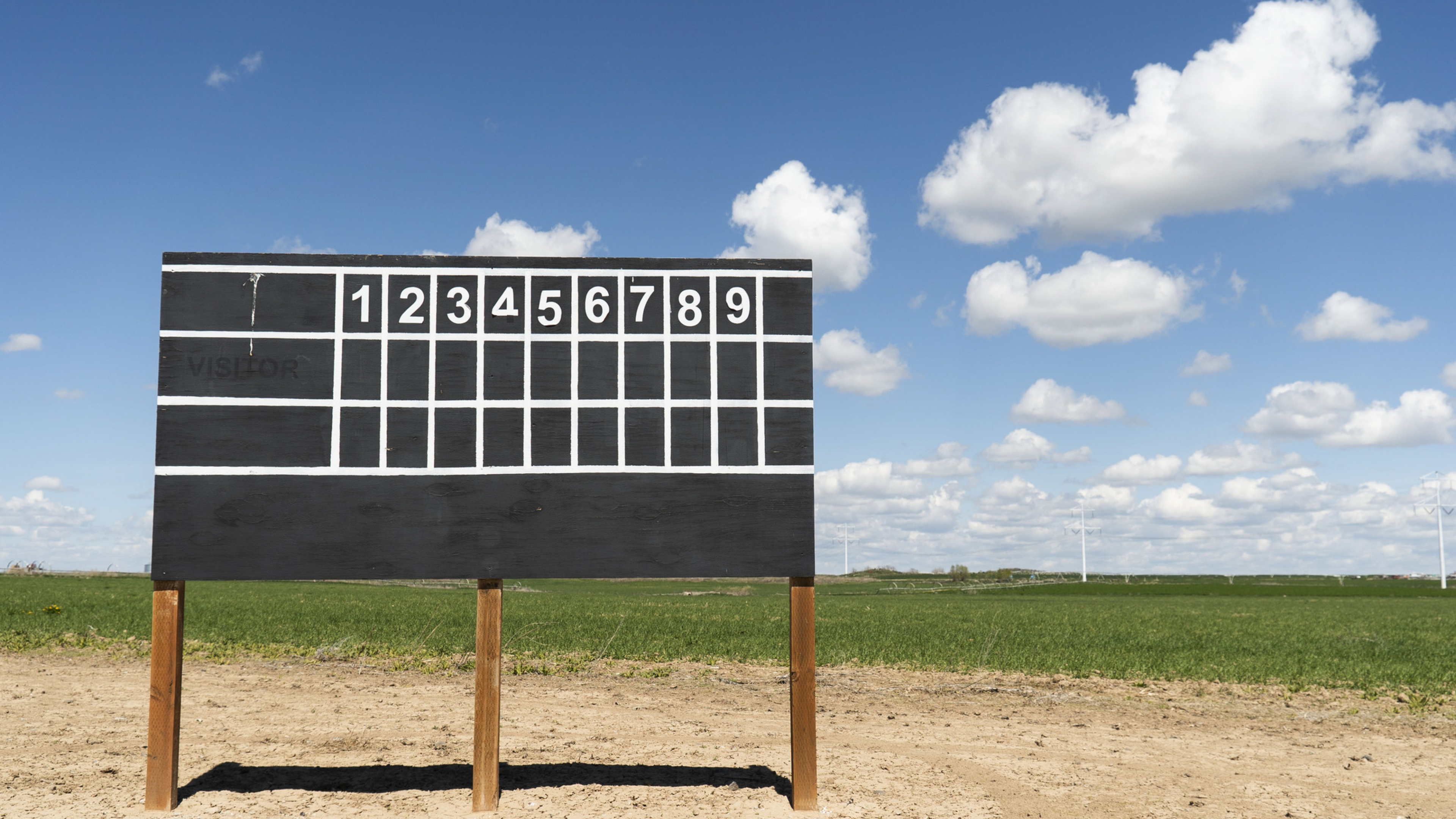 scoreboard with grass and sky behind