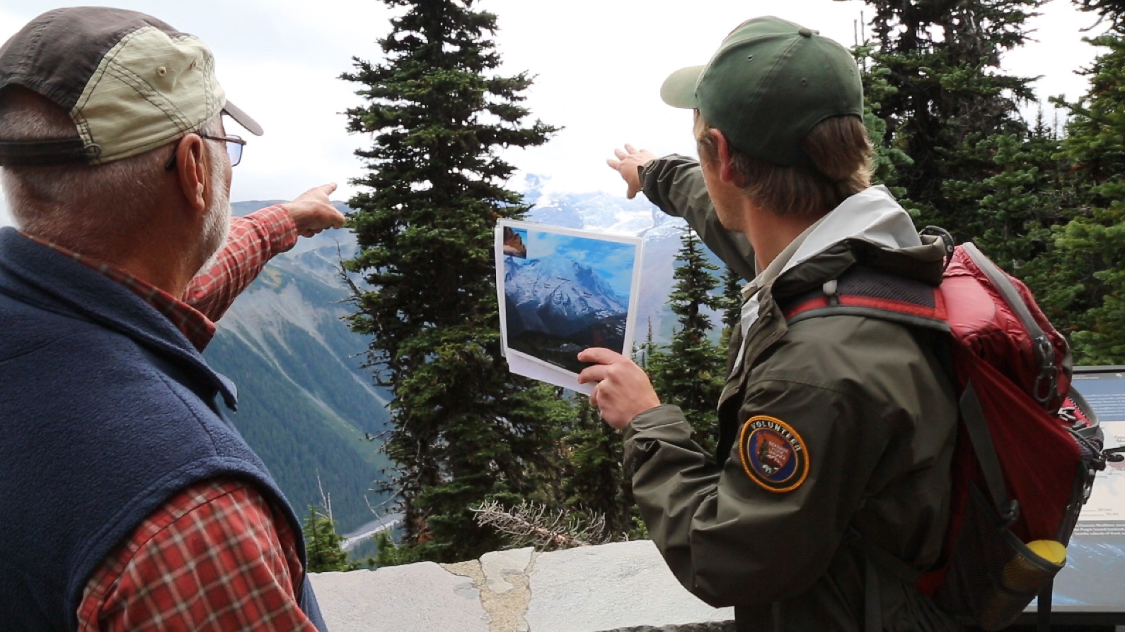 A young man in a volunteer green jacket points out a peak in the distance to a visitor, Mount Rainier National Park