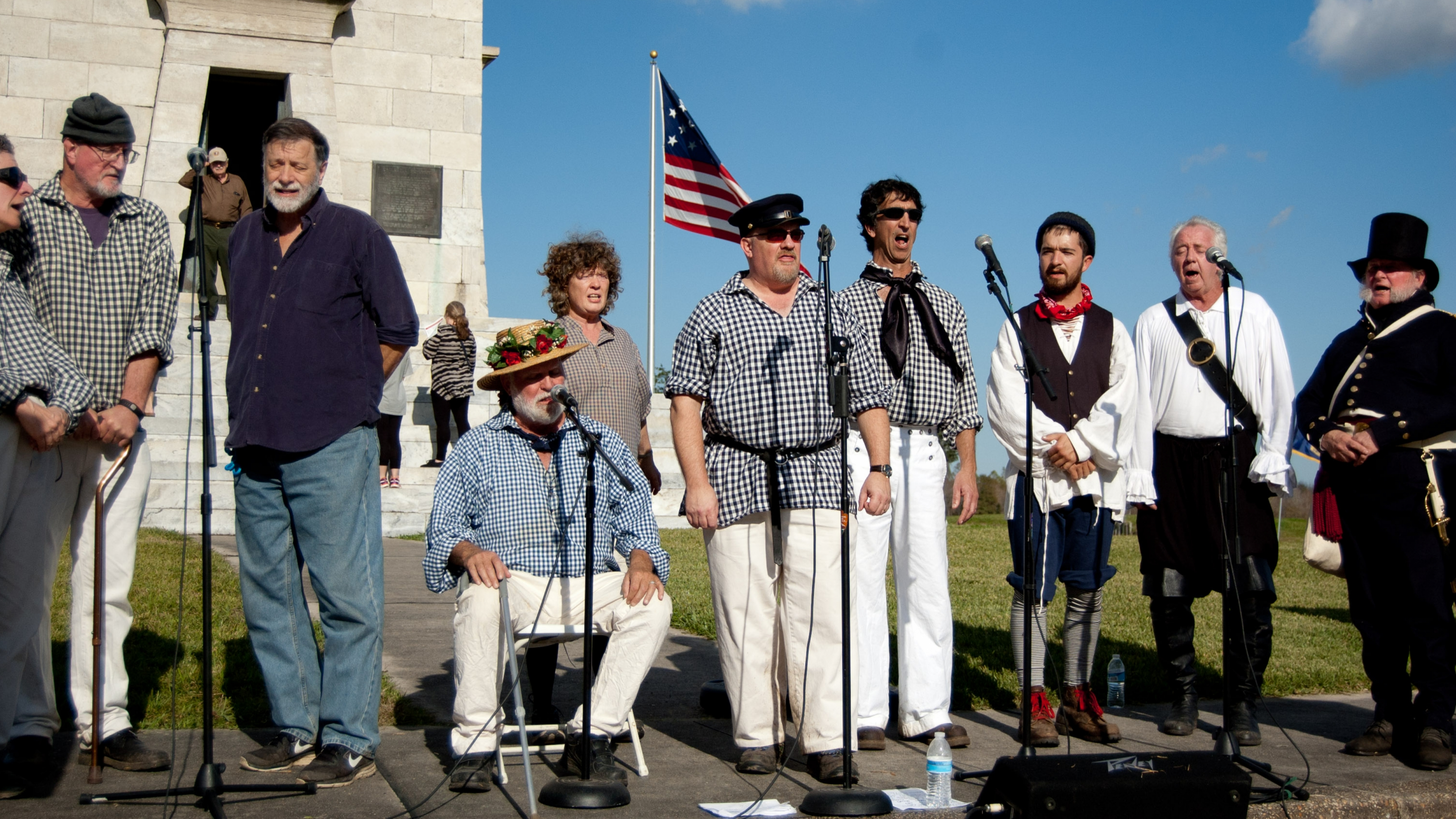 The men of No Quarter Shanty Krew singing outside in the sun at New Orleans Jazz National Historical Park