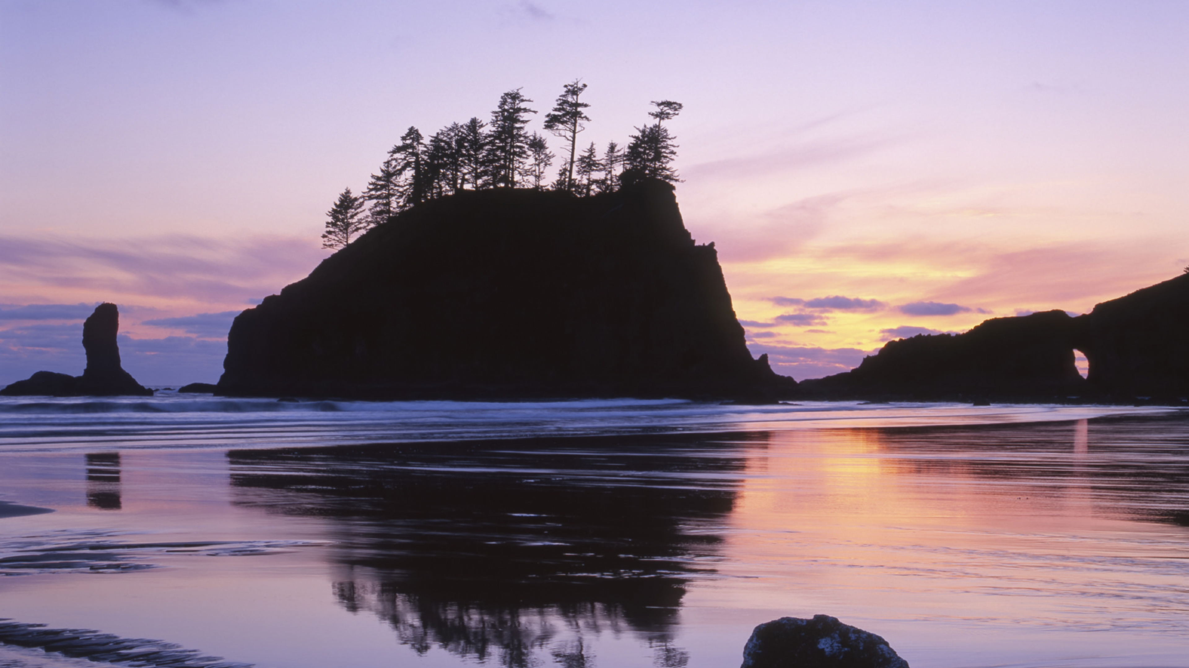 The colorful pink and purple sunset over the rocky islands on the shore of Olympic National Park