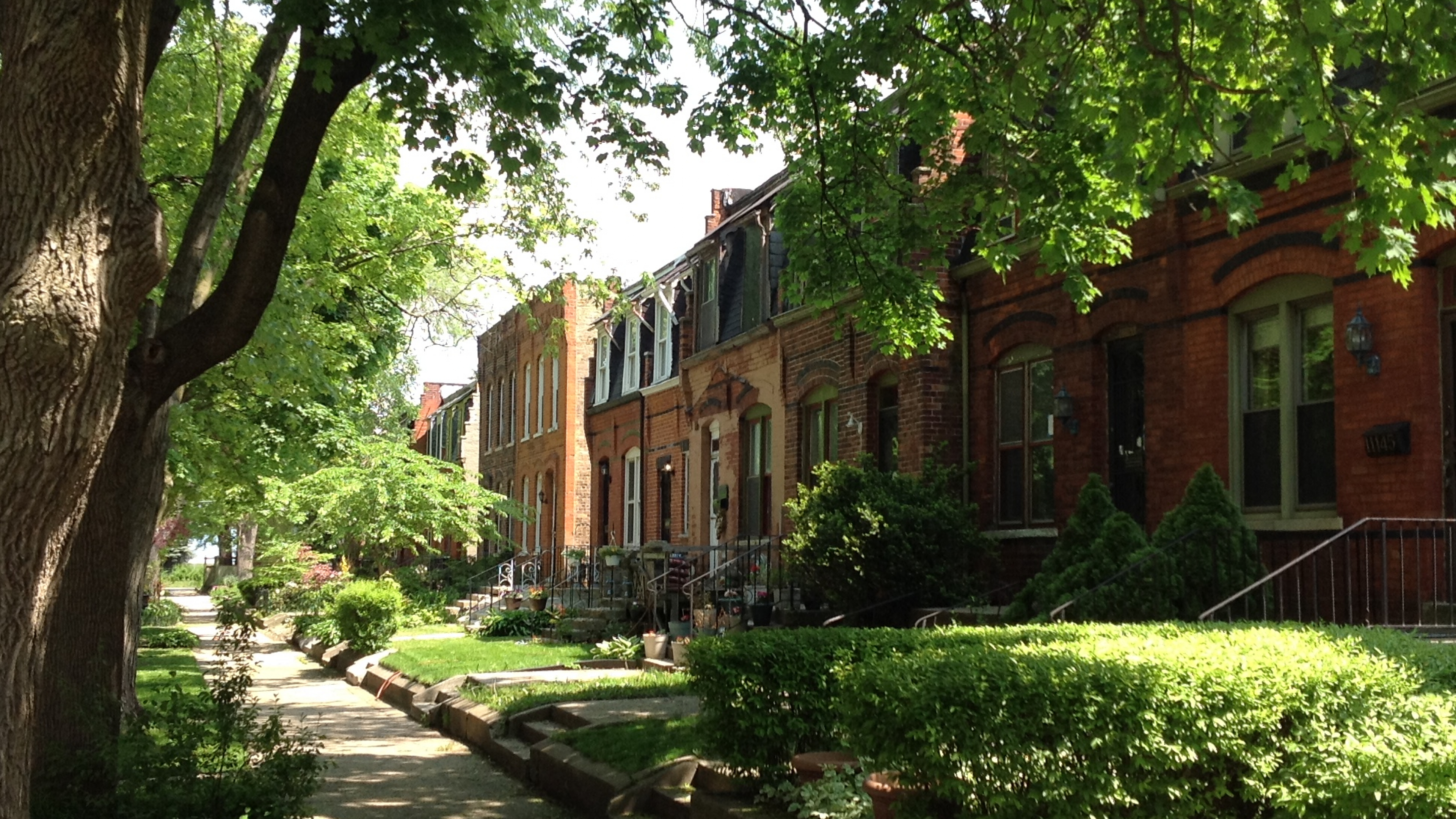 Brick homes lined along a road with green trees and lawns along Champlain Street at Pullman National Monument
