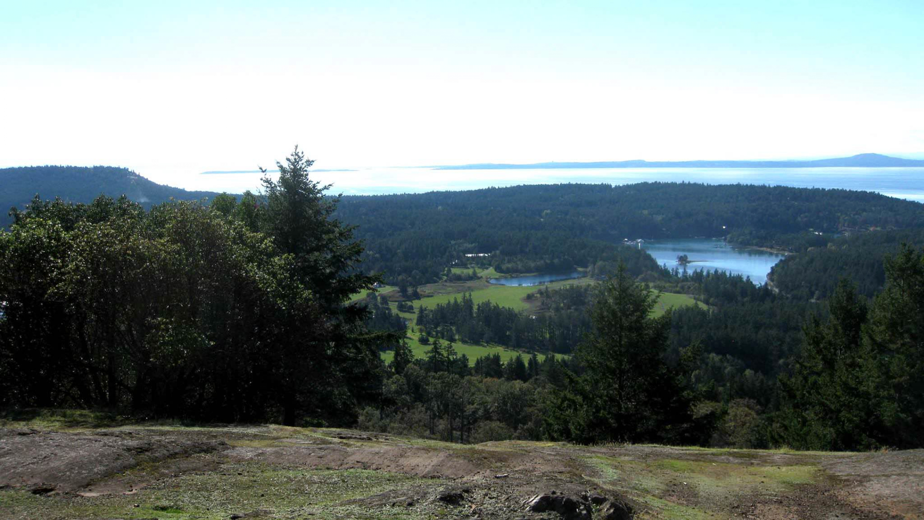 A look across the green-treed and blue-oceaned bay from a summit at San Juan Islands National Historical Park