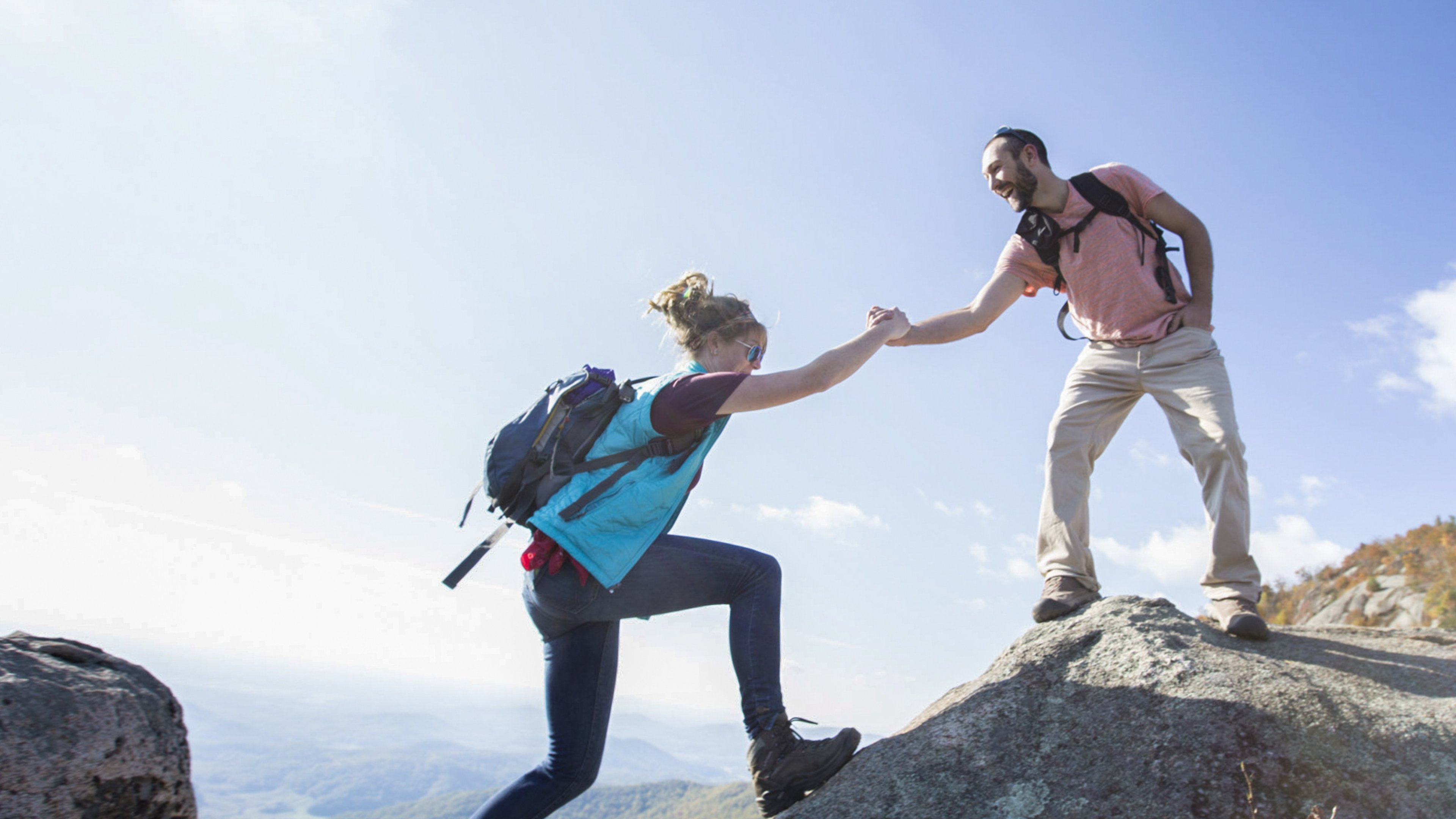 one hiker lends a hand to another to step between rocks