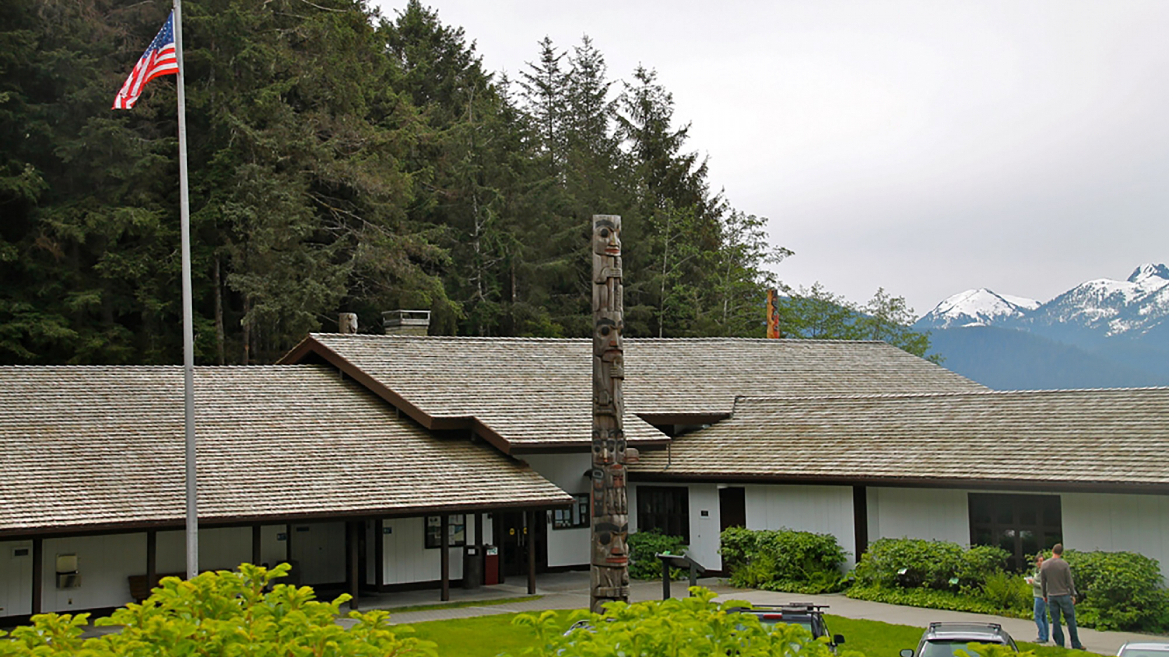 Visitor center with a totem pole and an American flag in front and mountains in the background.