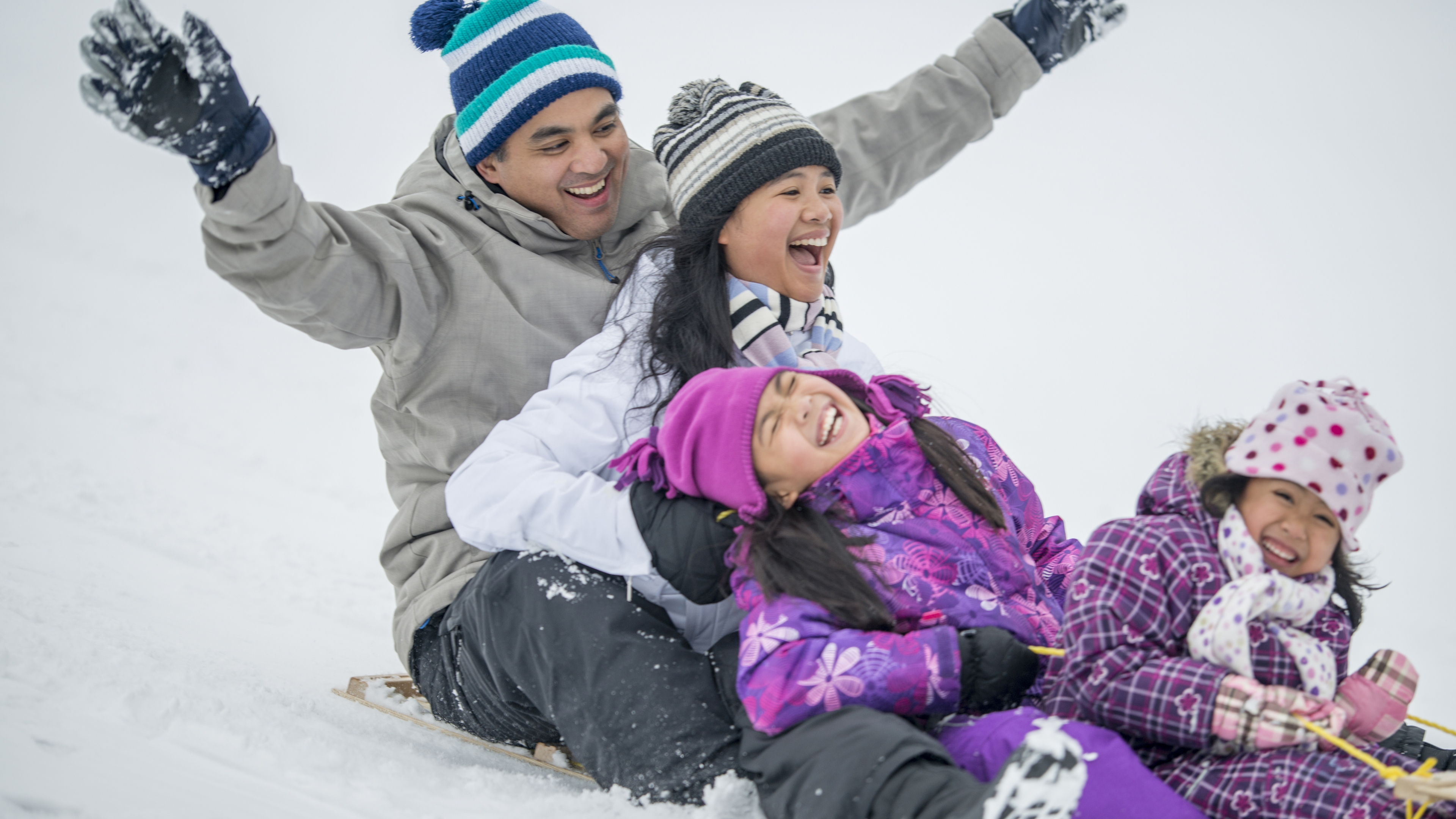 A laughing family of two parents and two young girls share a sled on a snow-covered hill.