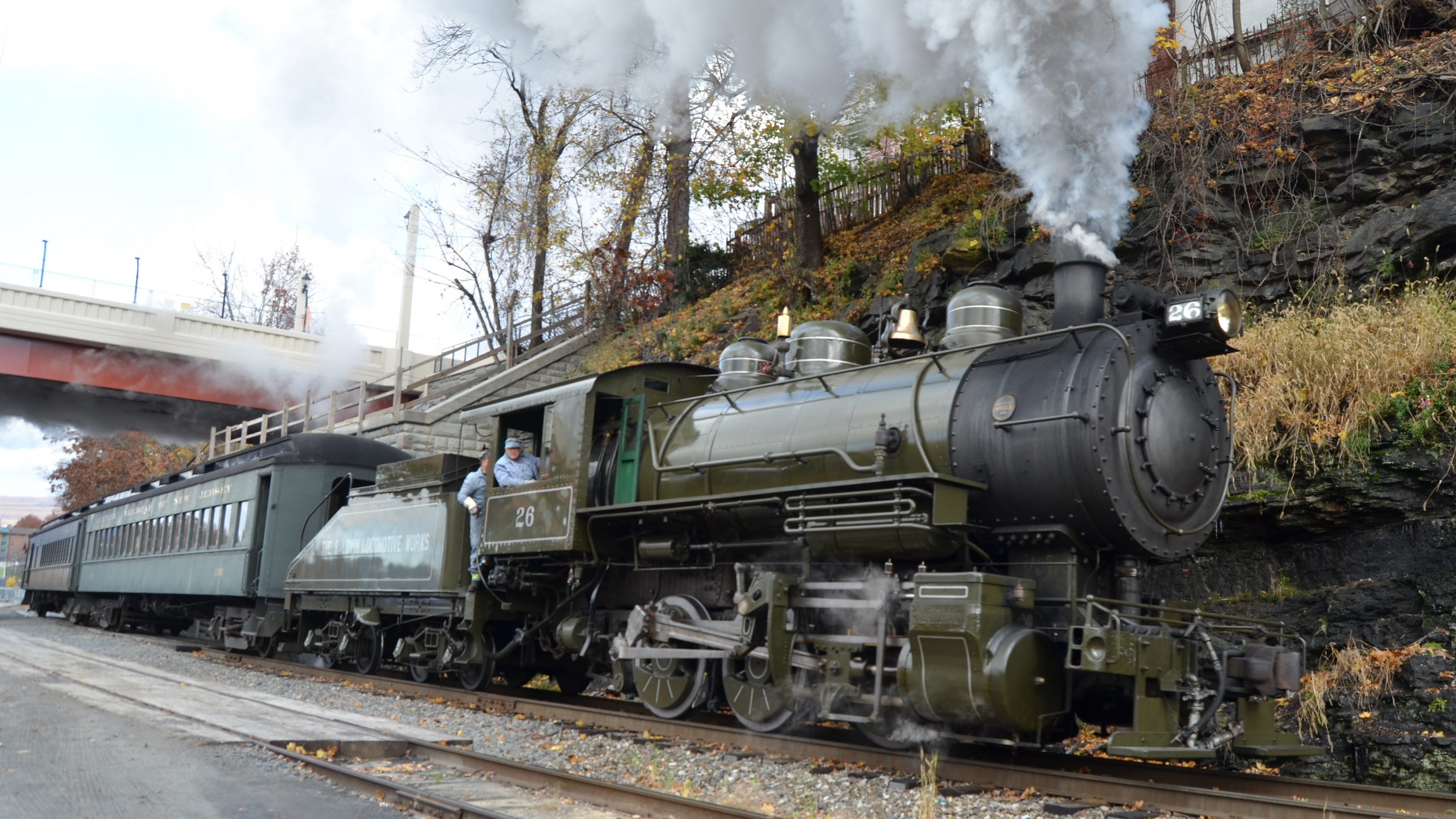 An olive-drab locomotive belches smoke as it travels on the tracks
