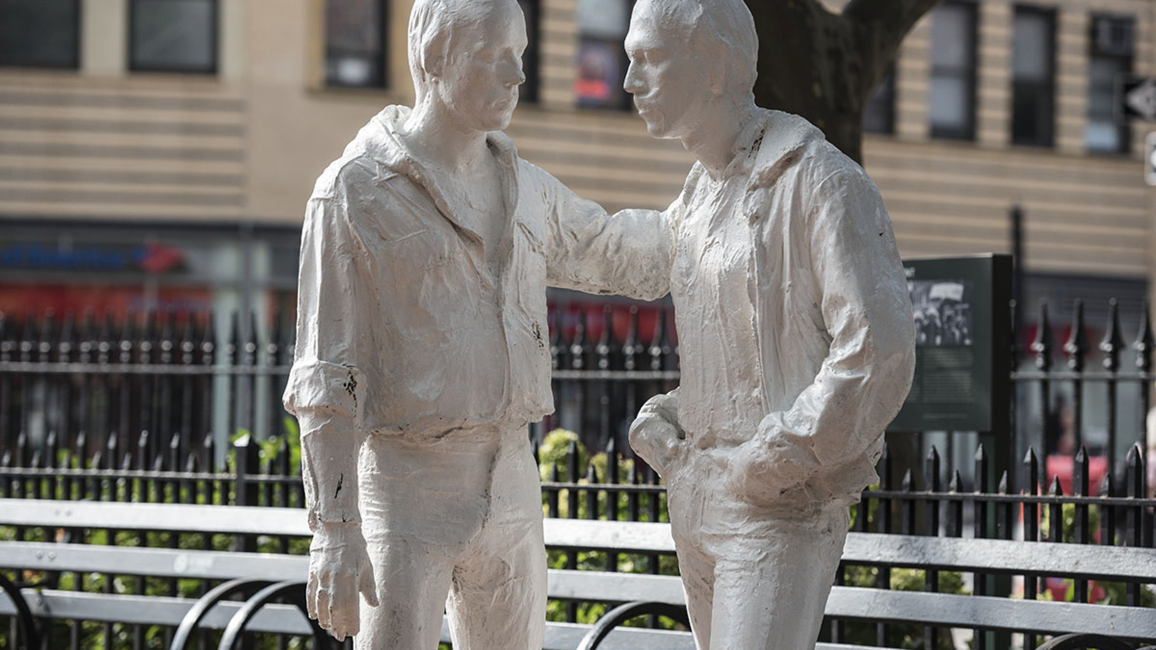 A white statue of two men at Christopher Park at Stonewall National Monument in New York