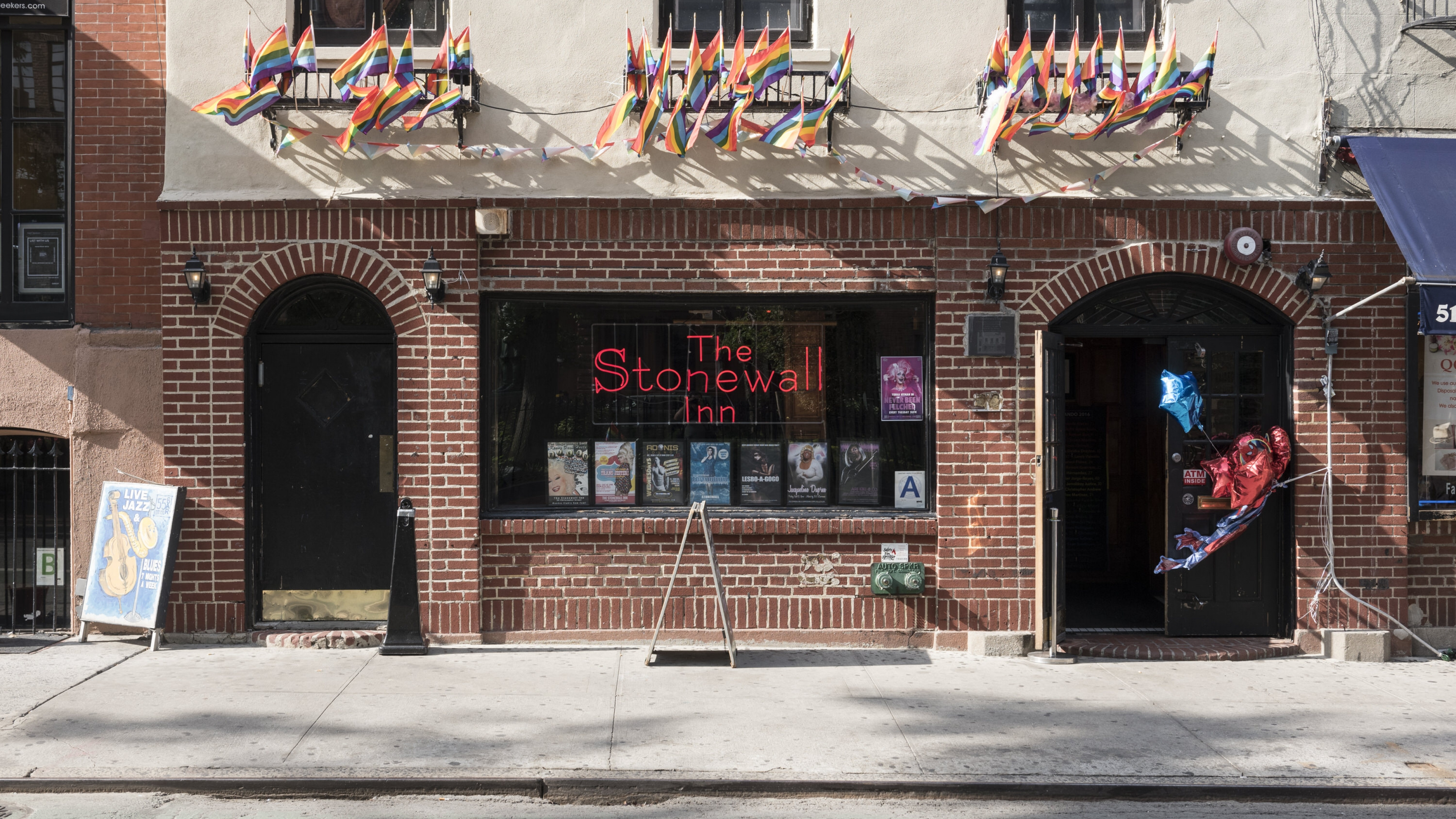 Front of the Stonewall Inn National Monument with rainbow flags blowing in the wind