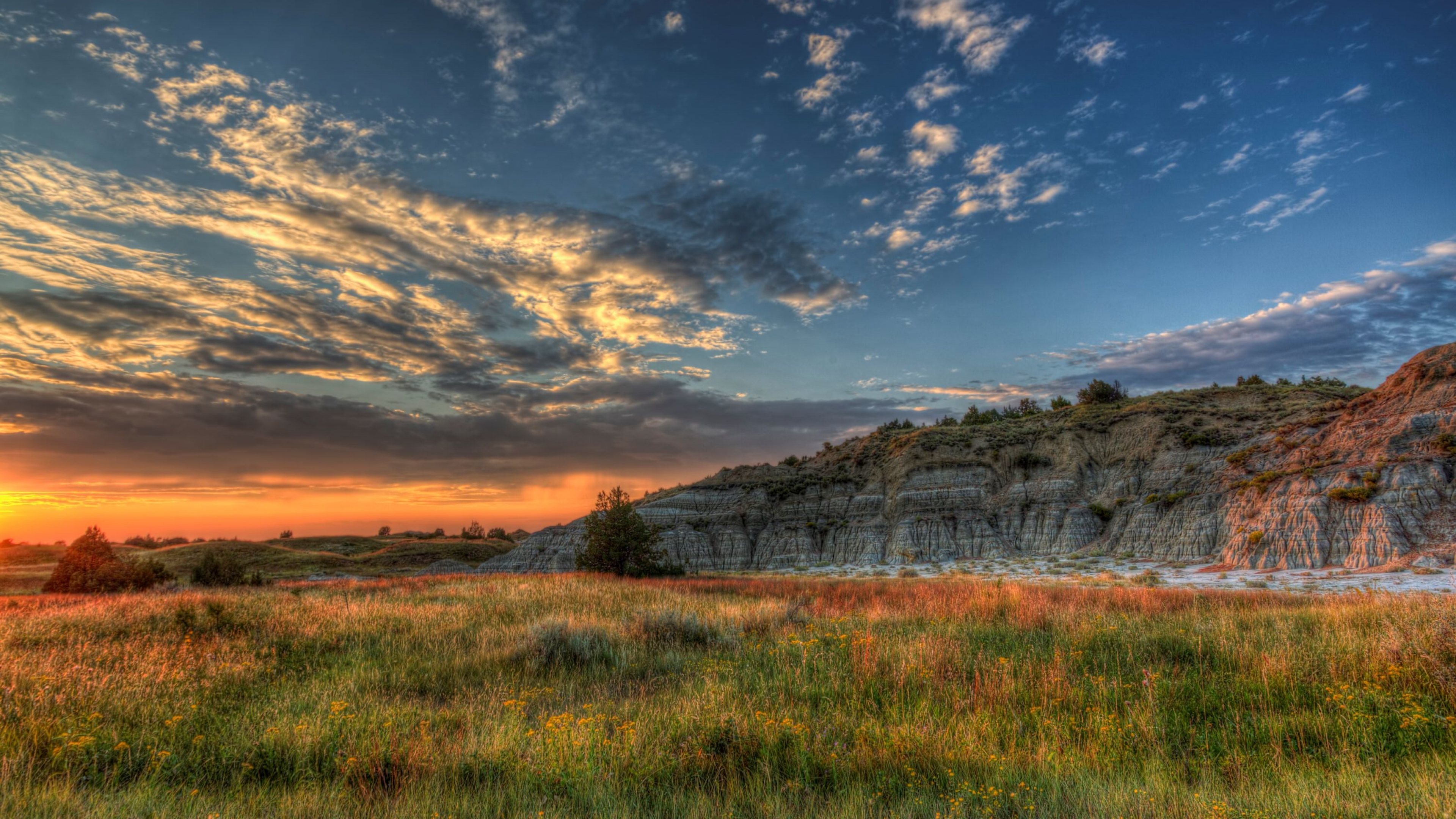 Colorful yellow and blue sunset shining golden light onto the green prairie and the white and red sandstone buttes of Theodore Roosevelt National Park