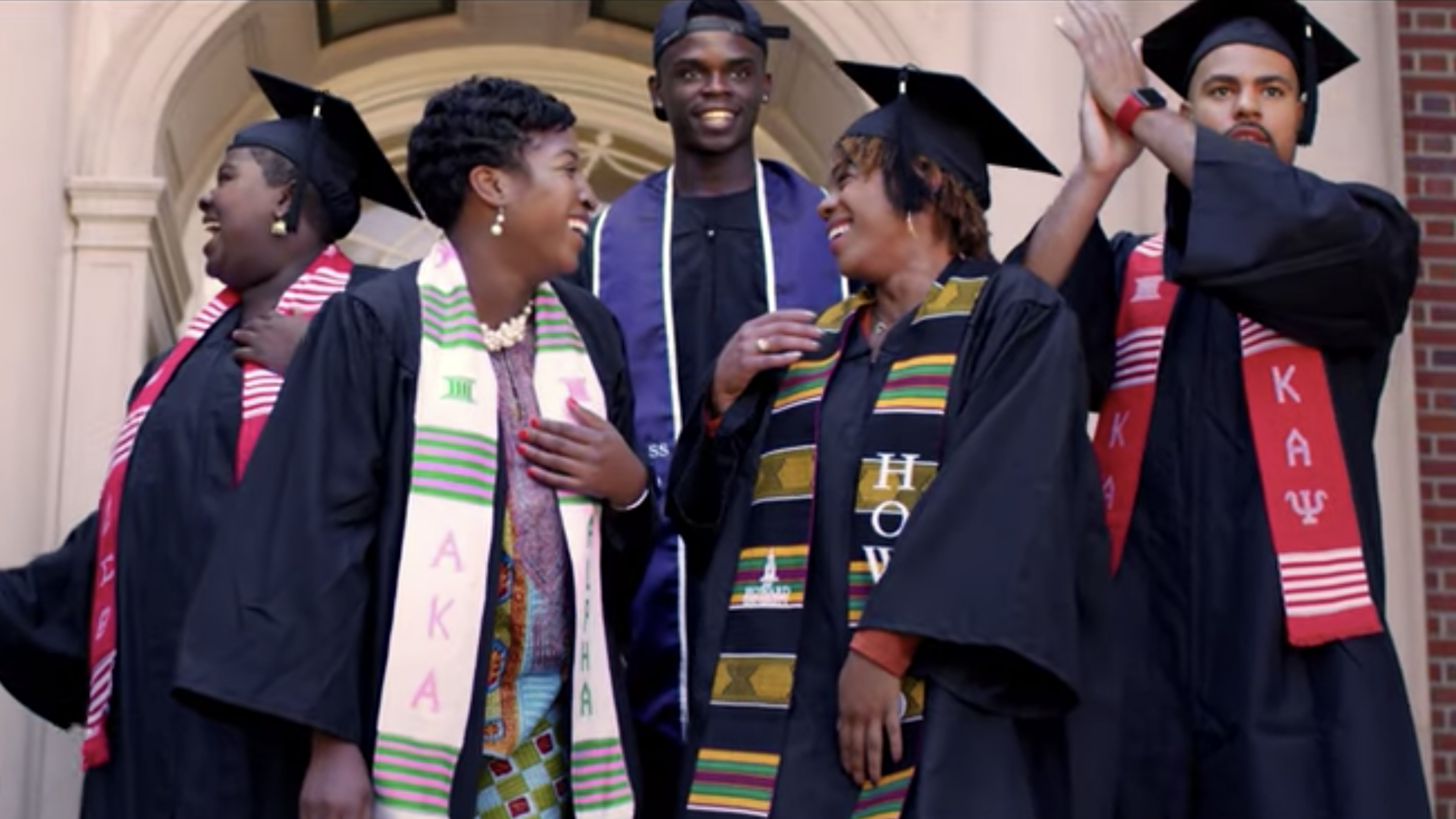 A group of graduates, dressed in caps and gowns, celebrate on the steps of a college