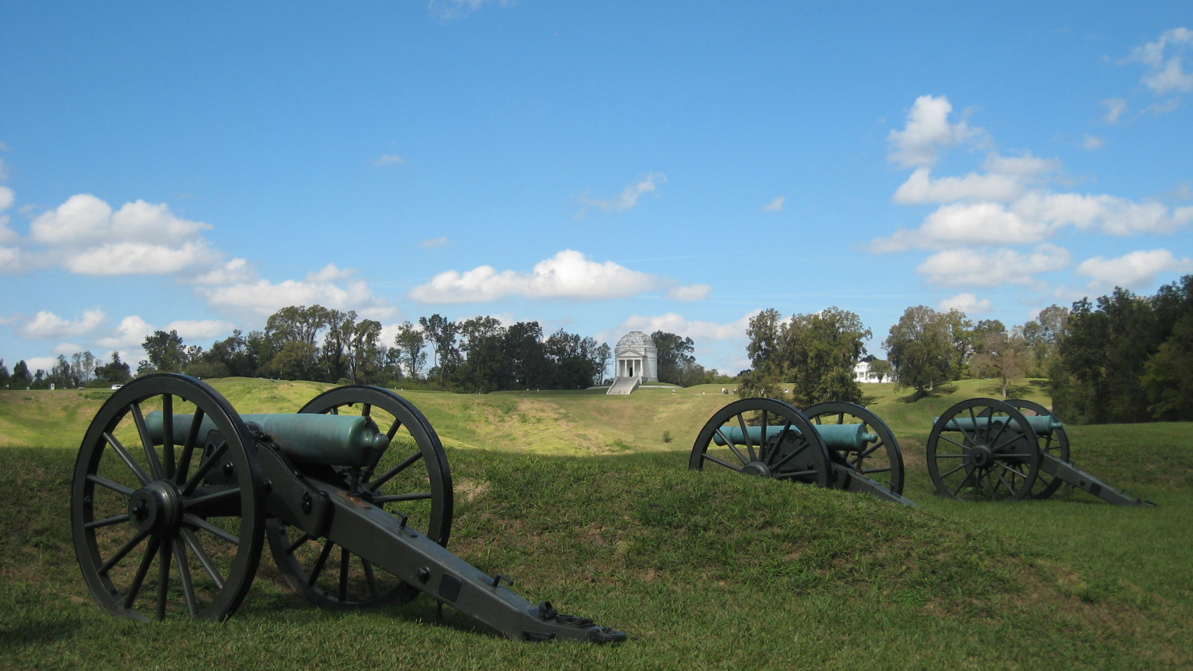 Three cannons in the green grass with a white roman-styled building in the horizon at Vicksburg National Military Park