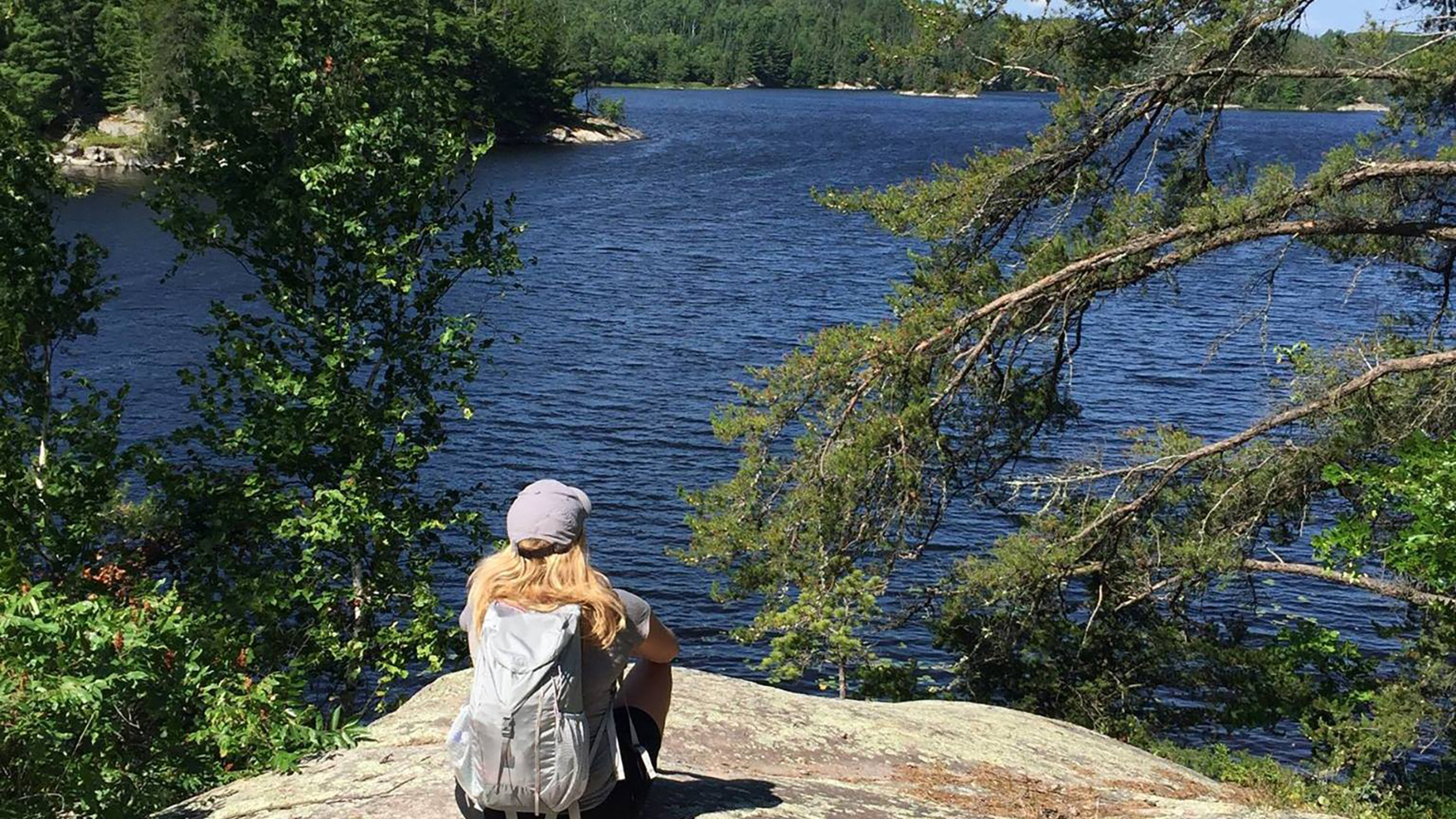 Christina sits and looks out on a lake from a high stony cliff