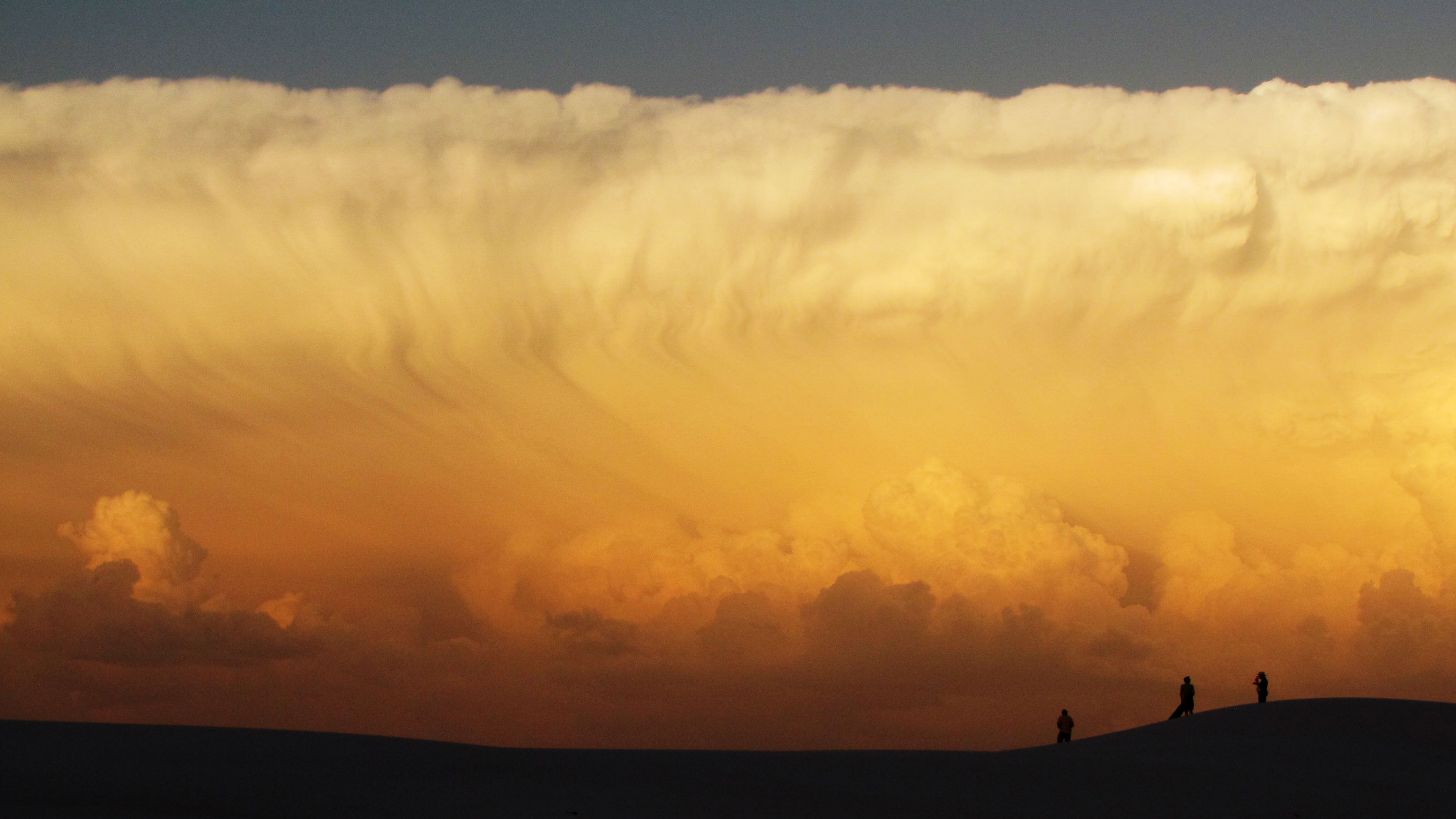 A wall of clouds lit orange and white by the setting sun at White Sands National Monument