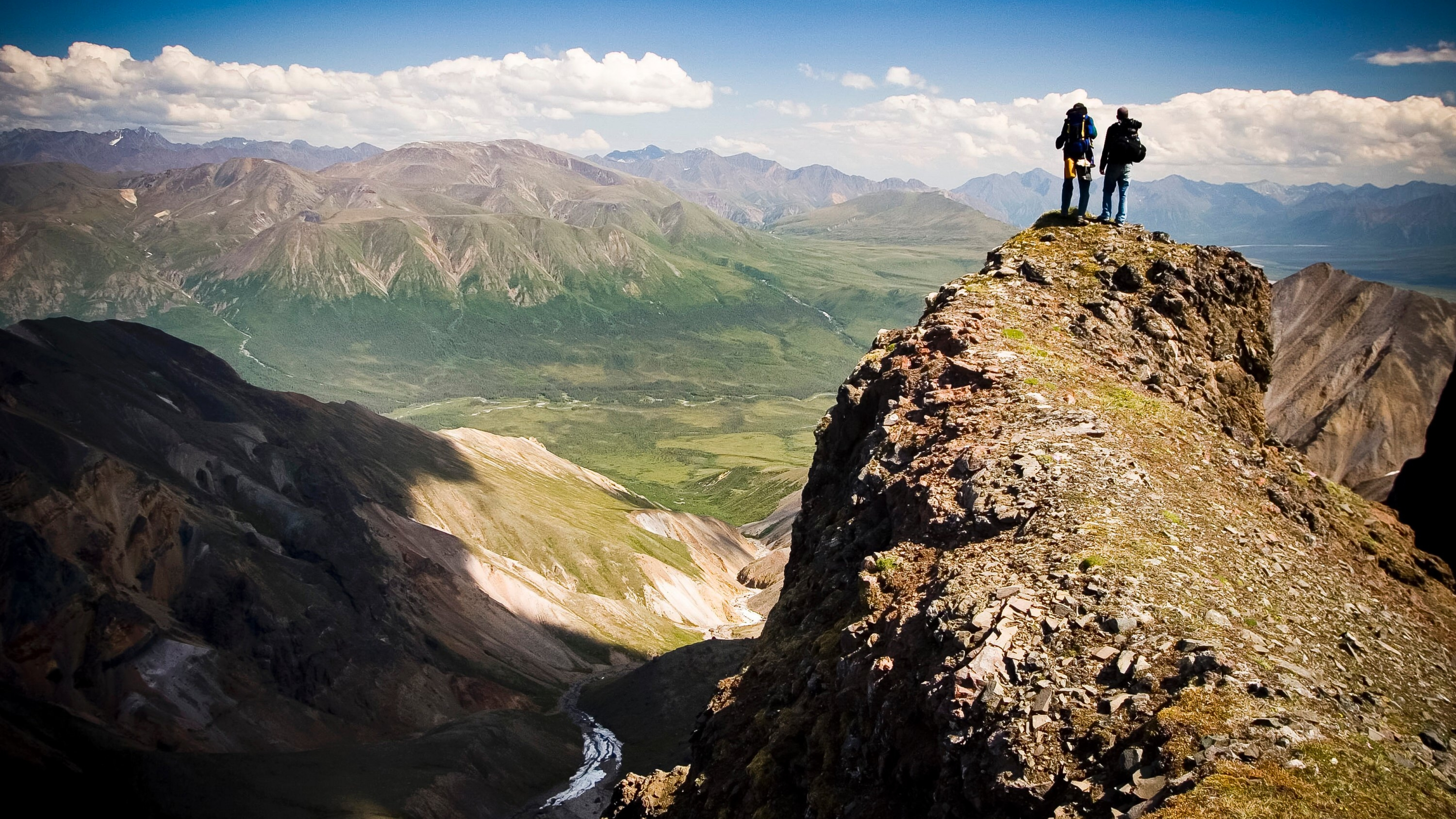 Two backpackers overlooking a valley on the Rambler Mine Route at Wrangell St.-Elias National Park & Preserve