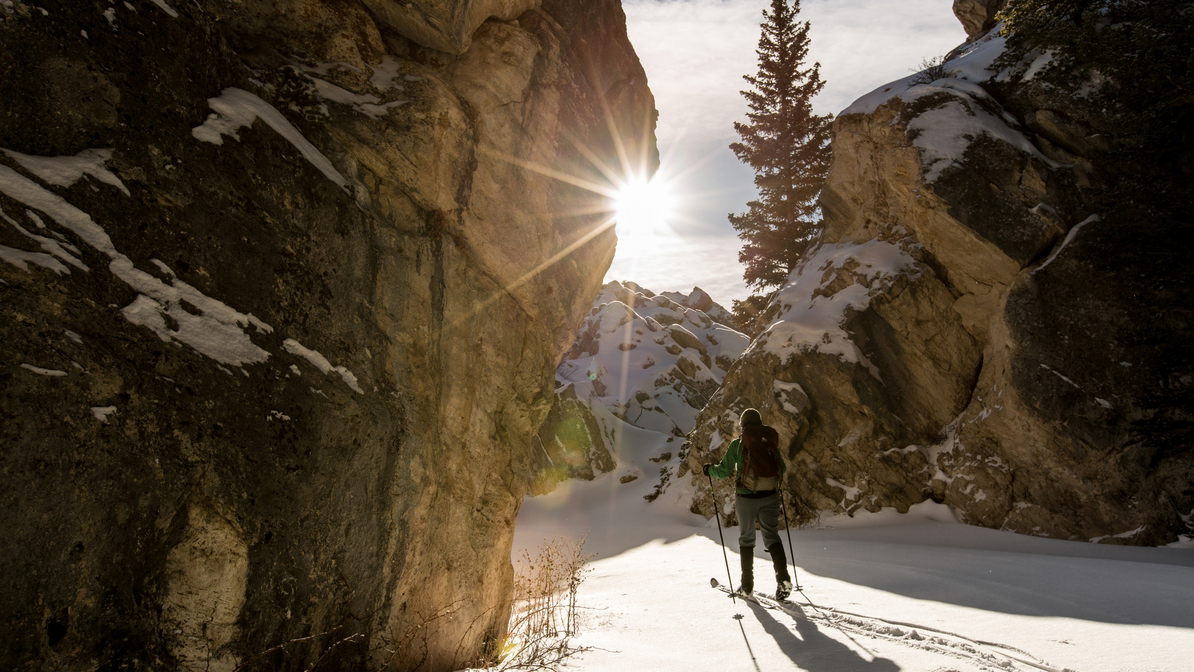 Person is skiing through large boulders of limestone with sun shine directly at her