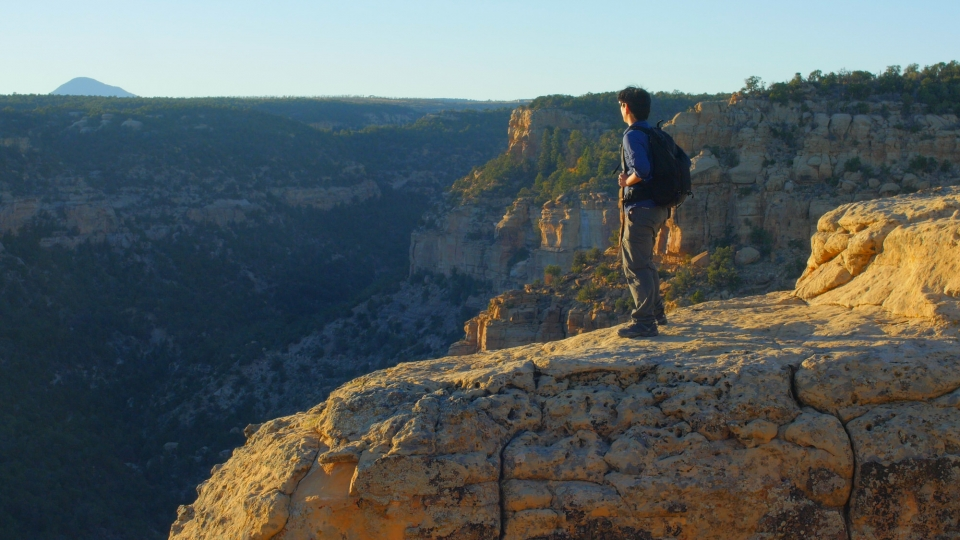 Andrew Lin standing at the edge of the overlook on top of the Mesa Verde cliffsm