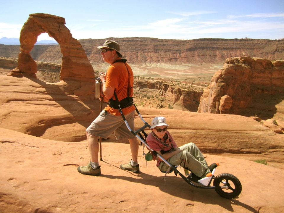 The national parks are for everyone--a man pulls a woman in a special wheelchair for hiking