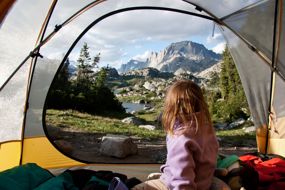 A child looks through a tent opening to a great expanse beyond
