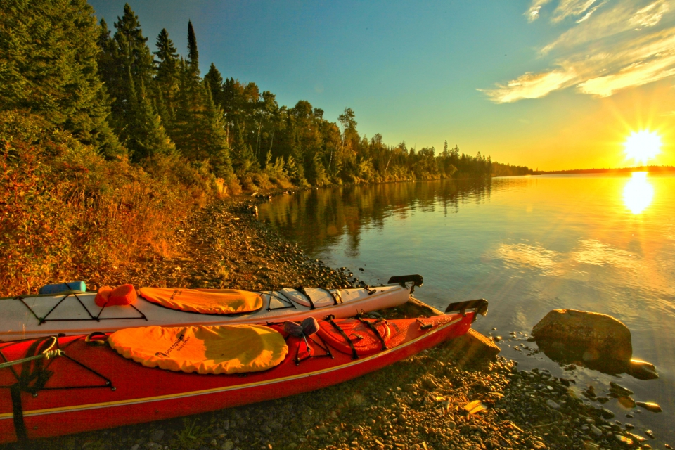 A pair of red kayaks sit near a sparkling lake at sunset