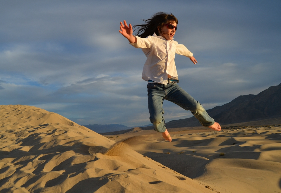 A woman jumps over rocks and sand in Death Valley