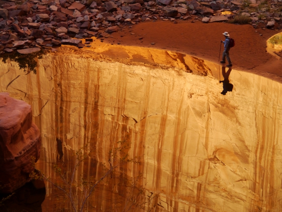 A hiker on a high ledge at Glen Canyon National Recreation Area