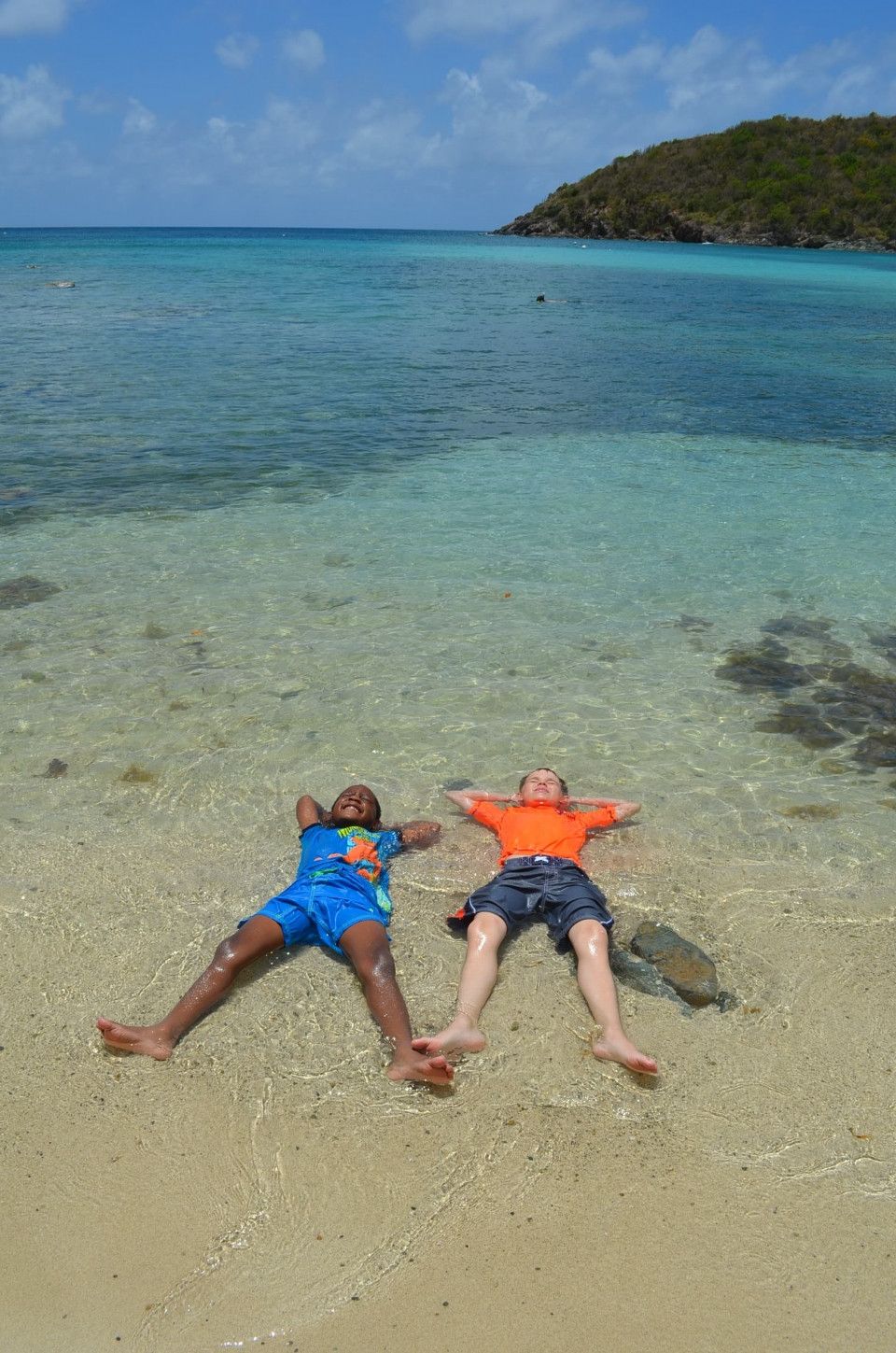 Every Kid in a Park winner image, One African American boy and one Caucasian boy lying on their backs in the water on a beach at the Virgin Islands