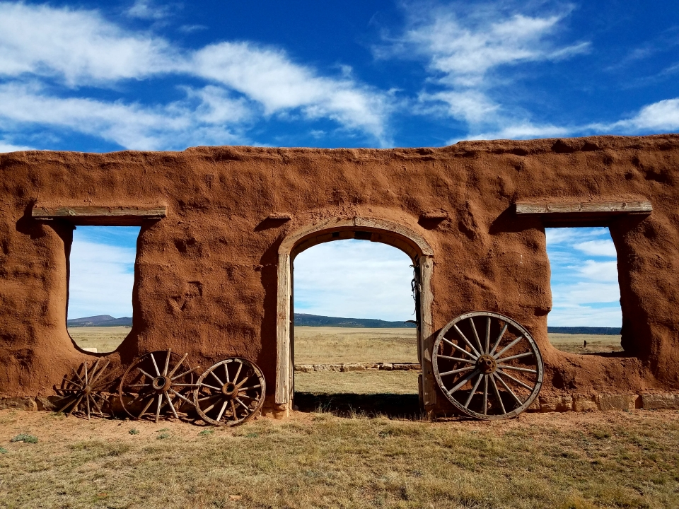 Wooden wagon wheels against the walls of a fort at Fort Union National Monument