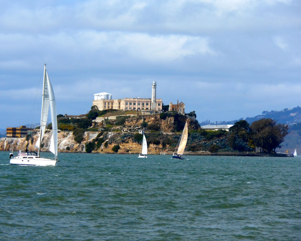 Lighthouse on Alcatraz Island with sailboats in the water on a sunny day