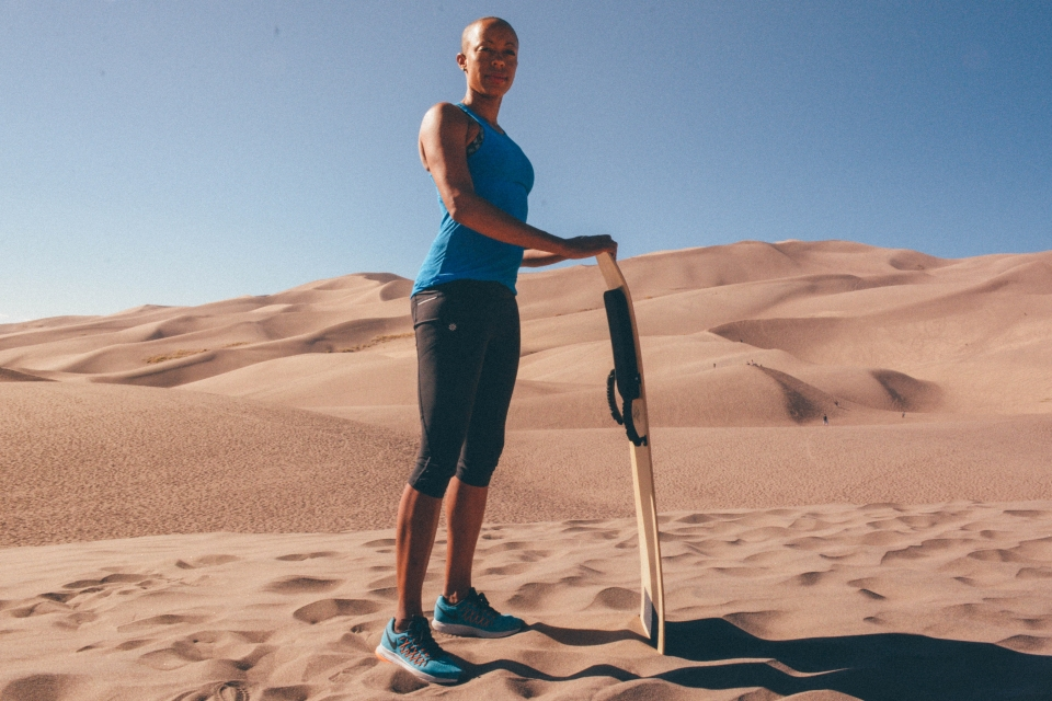 Andia with sandboard standing on sand dunes