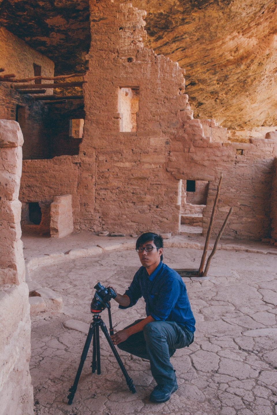 Andrew squatting with tripod in ruins of Mesa Verde National Park