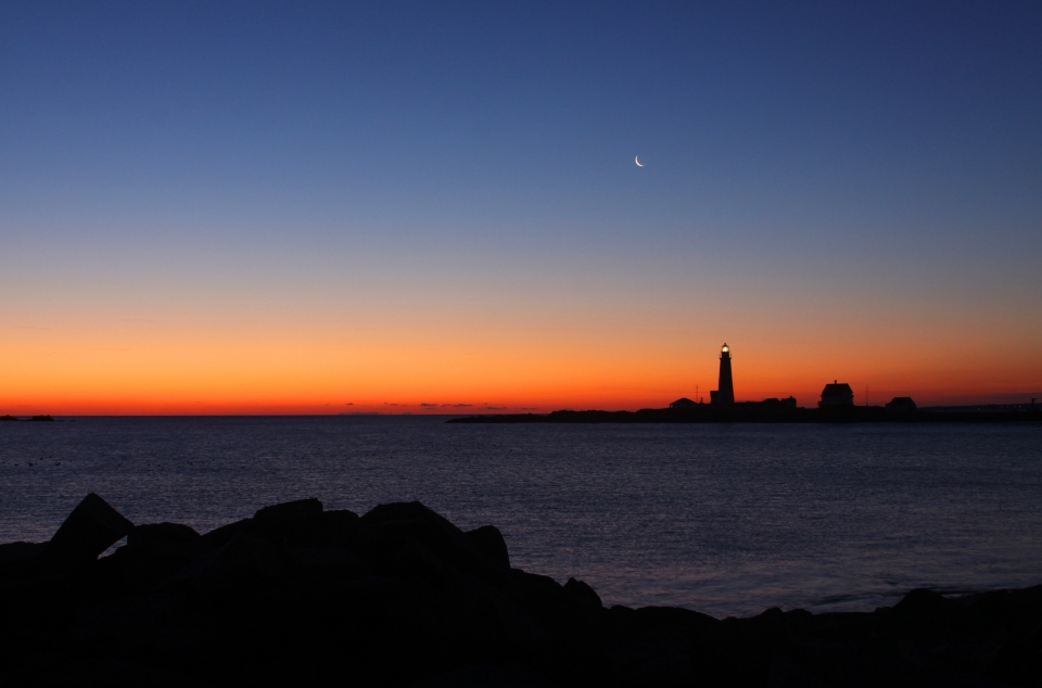 Lighthouse silhouette in the distance with the sun setting and the crescent moon above at Boston Harbor Islands National Recreation Area
