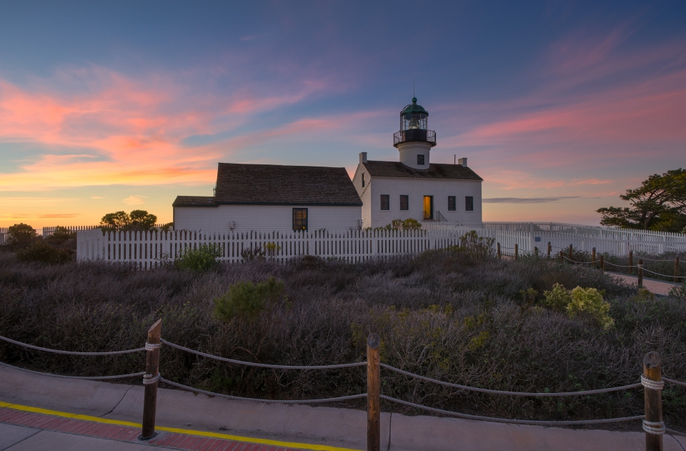 Lighthouse on land with colorful clouds behind at Cabrillo National Monument