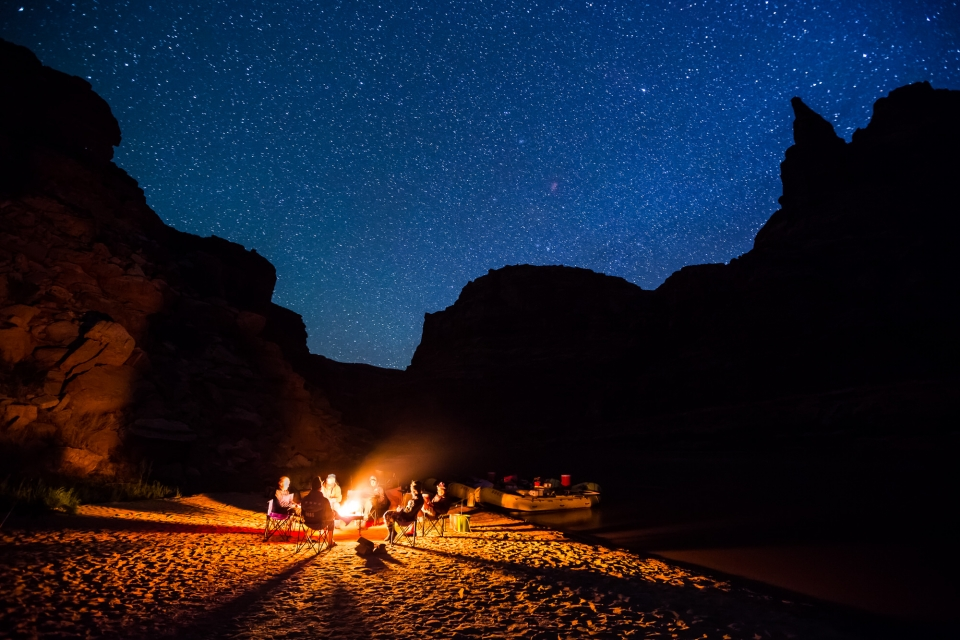 Group gathered around campfire under a starry sky at Canyonlands National Park