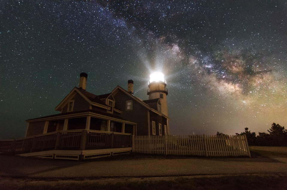 Lit lighthouse with stars and the Milky Way in the night sky behind it at Cape Cod National Seashore