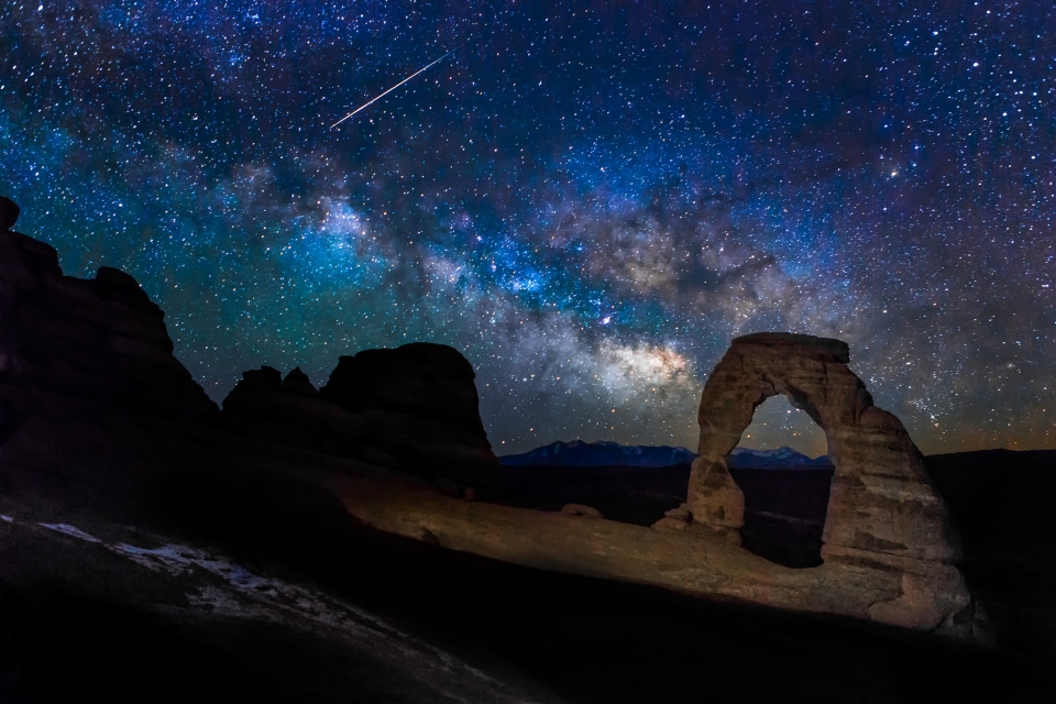 Milky way with shooting star over illuminated sandstone arch