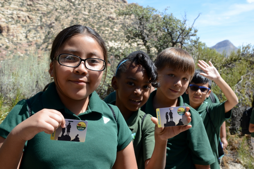 Diverse group of children in a national park holding their Every Kid In A Park pass.
